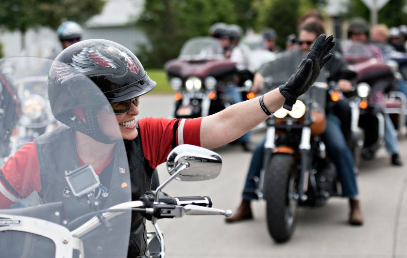 Senator Joni Ernst, a Republican from Iowa, waves to supporters as she rides the lead bike in a group motorcycle ride in Des Moines, Iowa, U.S., on Saturday, June 6, 2015.