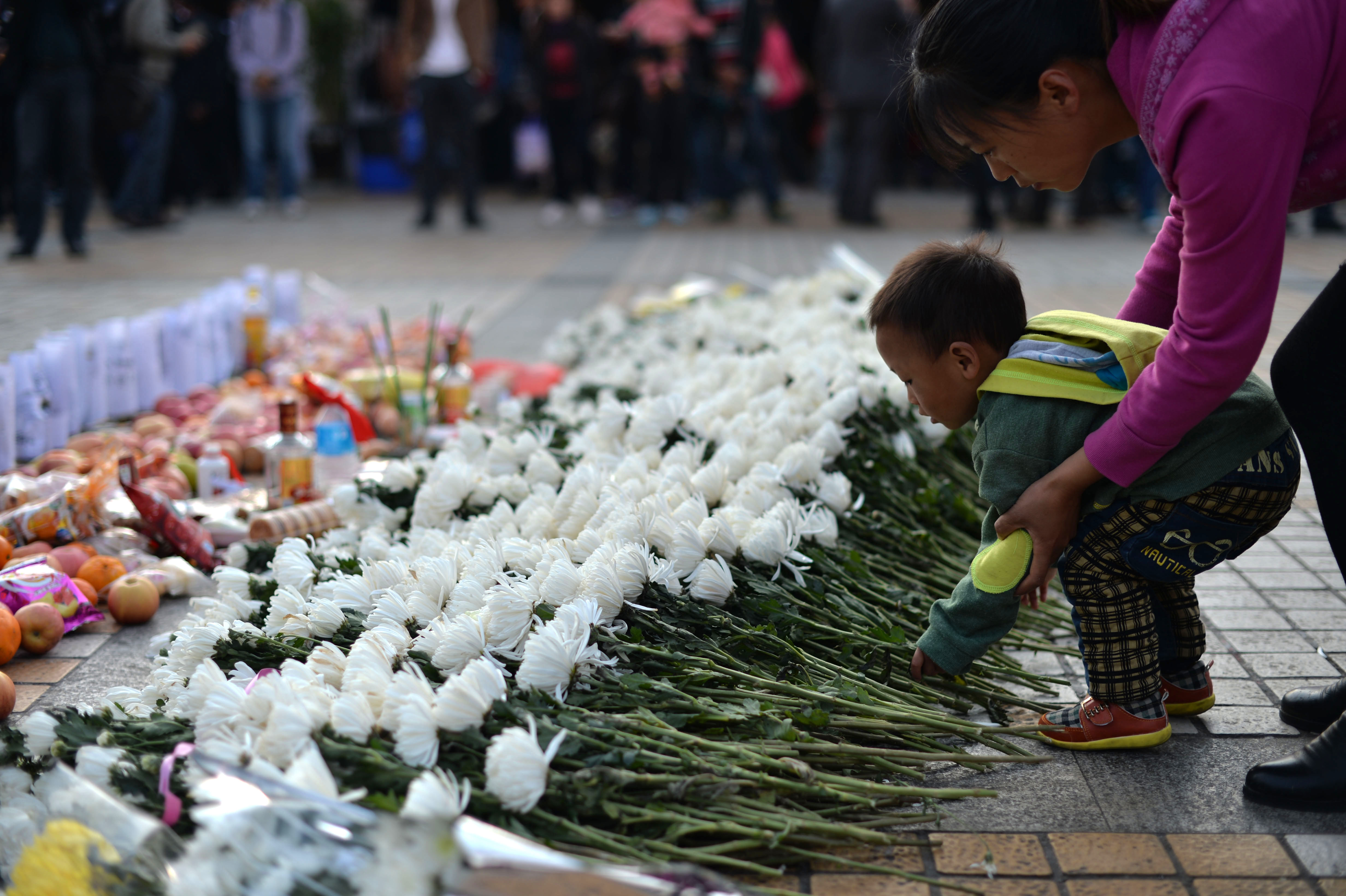 This picture taken on March 7, 2014, shows a child laying a flower at the scene of a terrorist attack at the main train station in Kunming, southwest China's Yunnan province. The attack in Kunming killed 29 people and injured 143