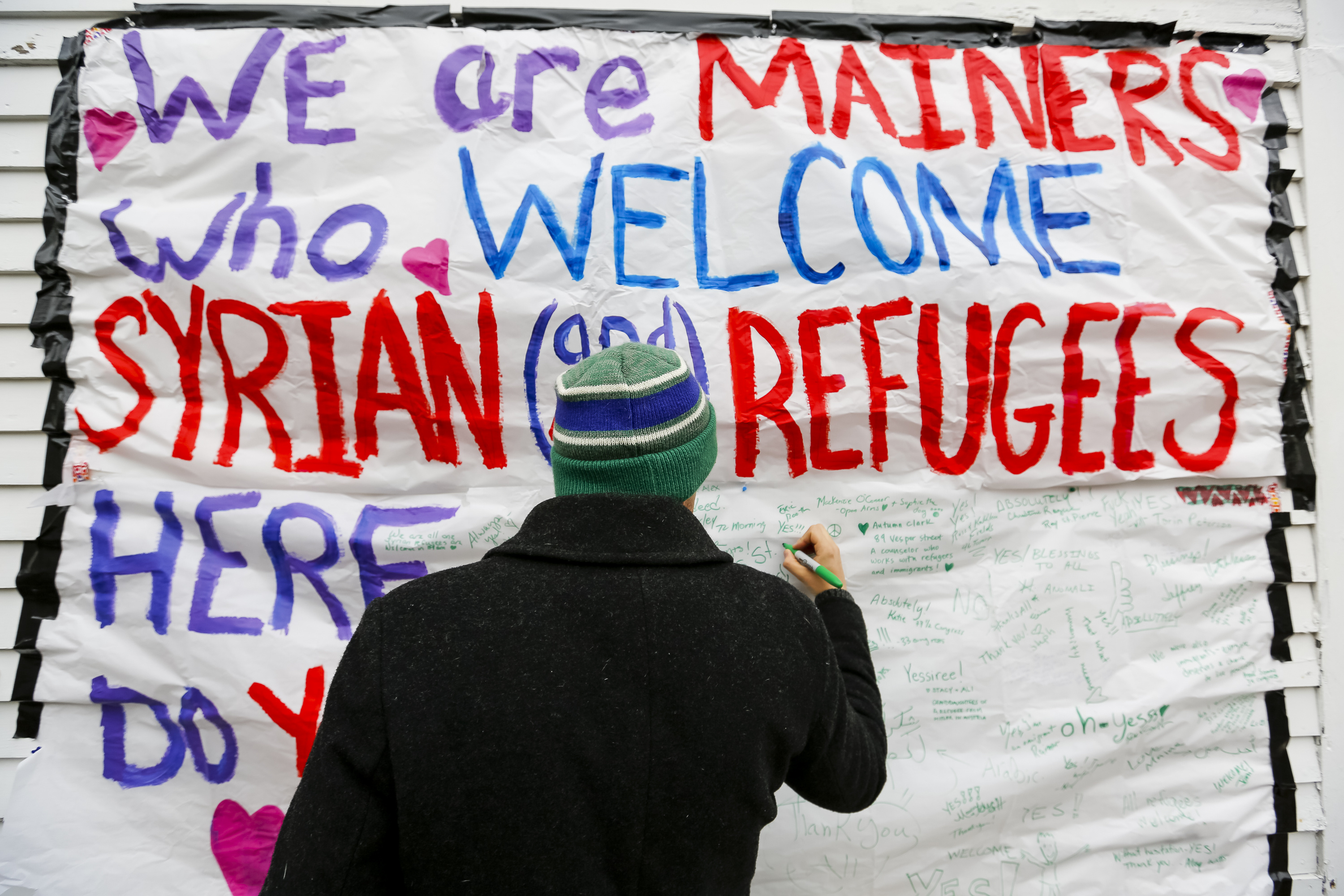 PORTLAND, ME - NOVEMBER 22: Munjoy Hill resident David Benson adds a message of support to a sign on Congress Street calling for a welcoming attitude toward the prospect of Syrian refugees. Benson's completed message reads,  Yes!!! Open arms!!!  Portland Press Herald—Press Herald via Getty Images