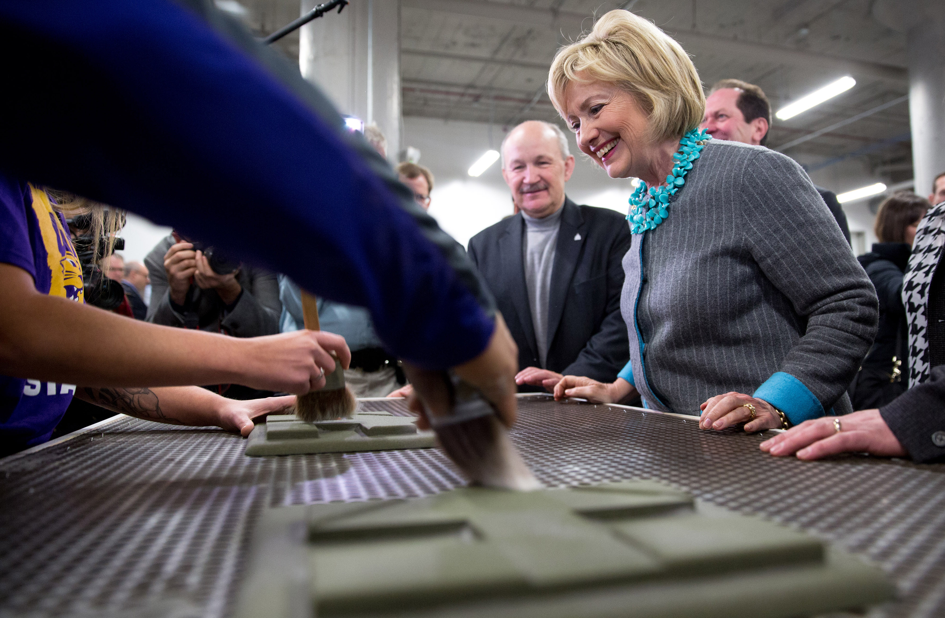 Hillary Clinton, former Secretary of State and 2016 Democratic presidential candidate, watches as students clean off 3D printed campaign logos made for her during a tour of the University of Northern Iowa's Additive Manufacturing Center at Cedar Valley TechWorks in Waterloo, Iowa, U.S., on Wednesday, Dec. 9, 2015.