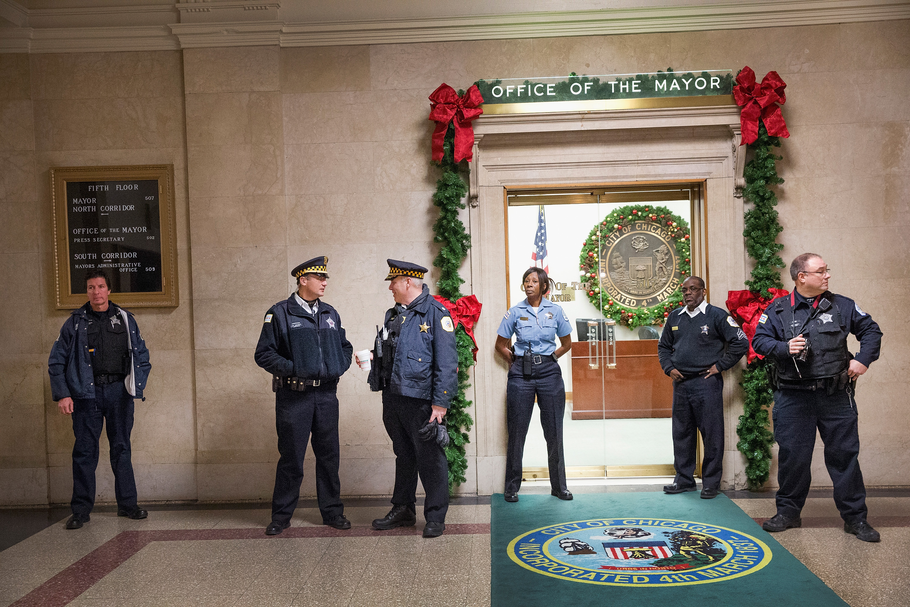 Police guard the entrance to the office of Mayor Rahm Emanuel as demonstrators calling for his resignation protest nearby on December 31, 2015 in Chicago, Illinois. The shooting deaths by police of a 19-year-old college student Quintonio LeGrier and his 55-year-old neighbor Bettie Jones and a recently released video showing the shooting of 17-year-old Laquan McDonald by Chicago Police officer Jason Van Dyke have sparked dozens of protests in the city. Yesterday Emanuel announced several changes that would take place in the police department with the hope of preventing future incidents.  (Photo by Scott Olson/Getty Images)