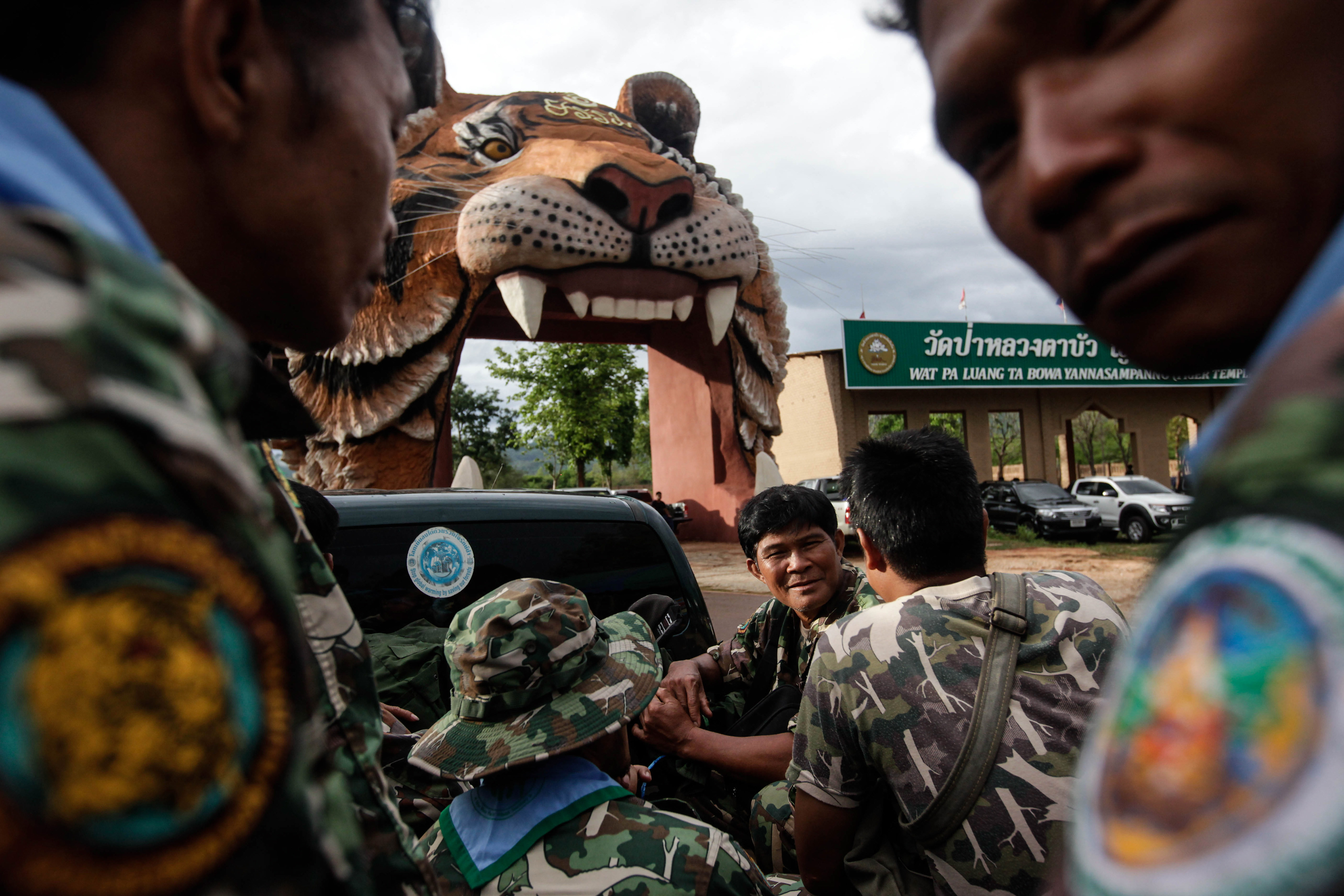 Thai DNP officers sit on a truck at the entrance of Wat Pha Luang Ta Bua Yanasampanno, or the Tiger Temple, on June 1, 2016, in Kanchanaburi province, Thailand. Wildlife authorities in Thailand have shut the temple down following accusations the monks were illegally breeding and trafficking endangered animals