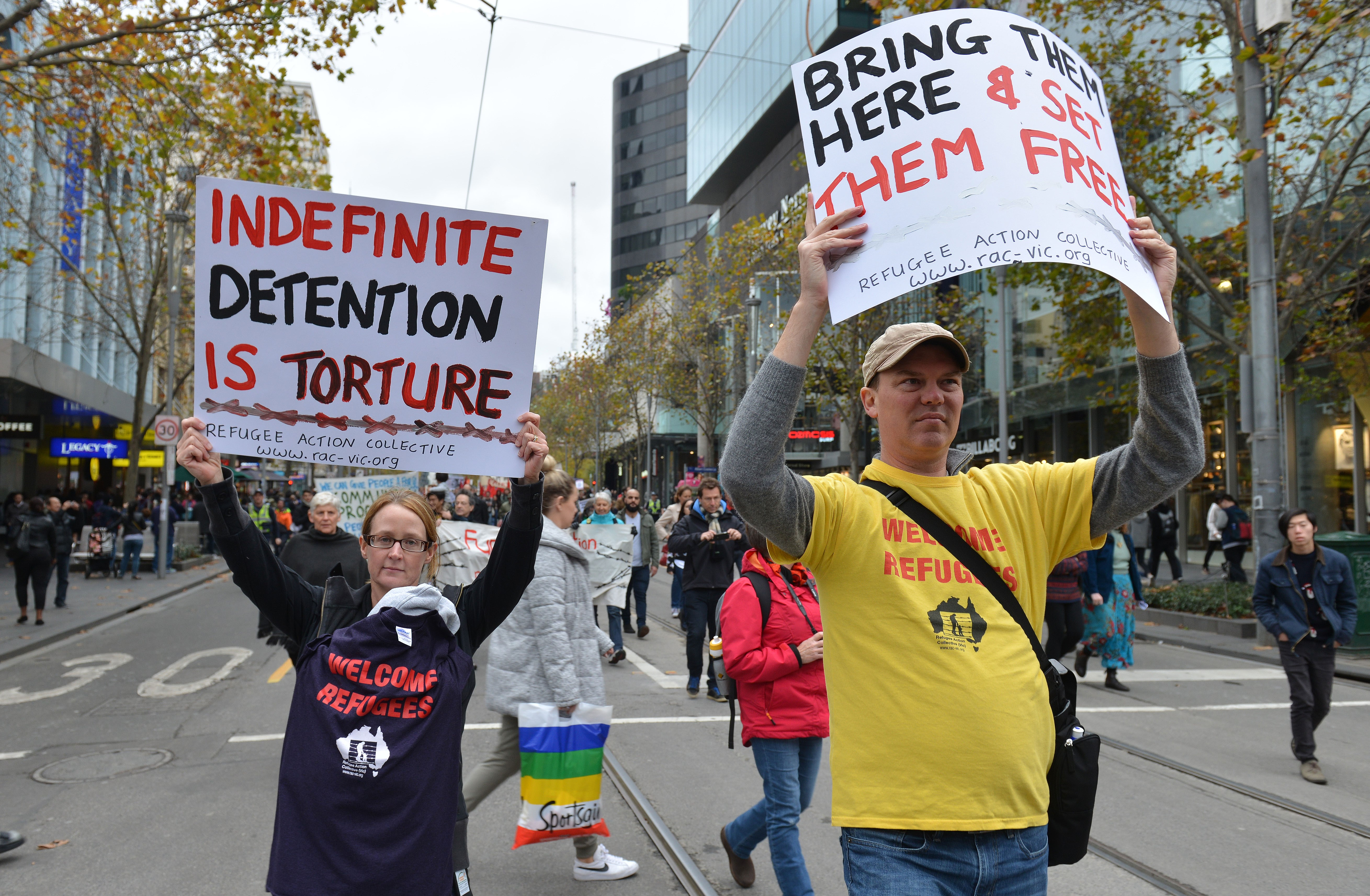Australians hold banners as they attend a demonstration within the 'International Migrant day' in Melbourne, Australia on June 18, 2016.