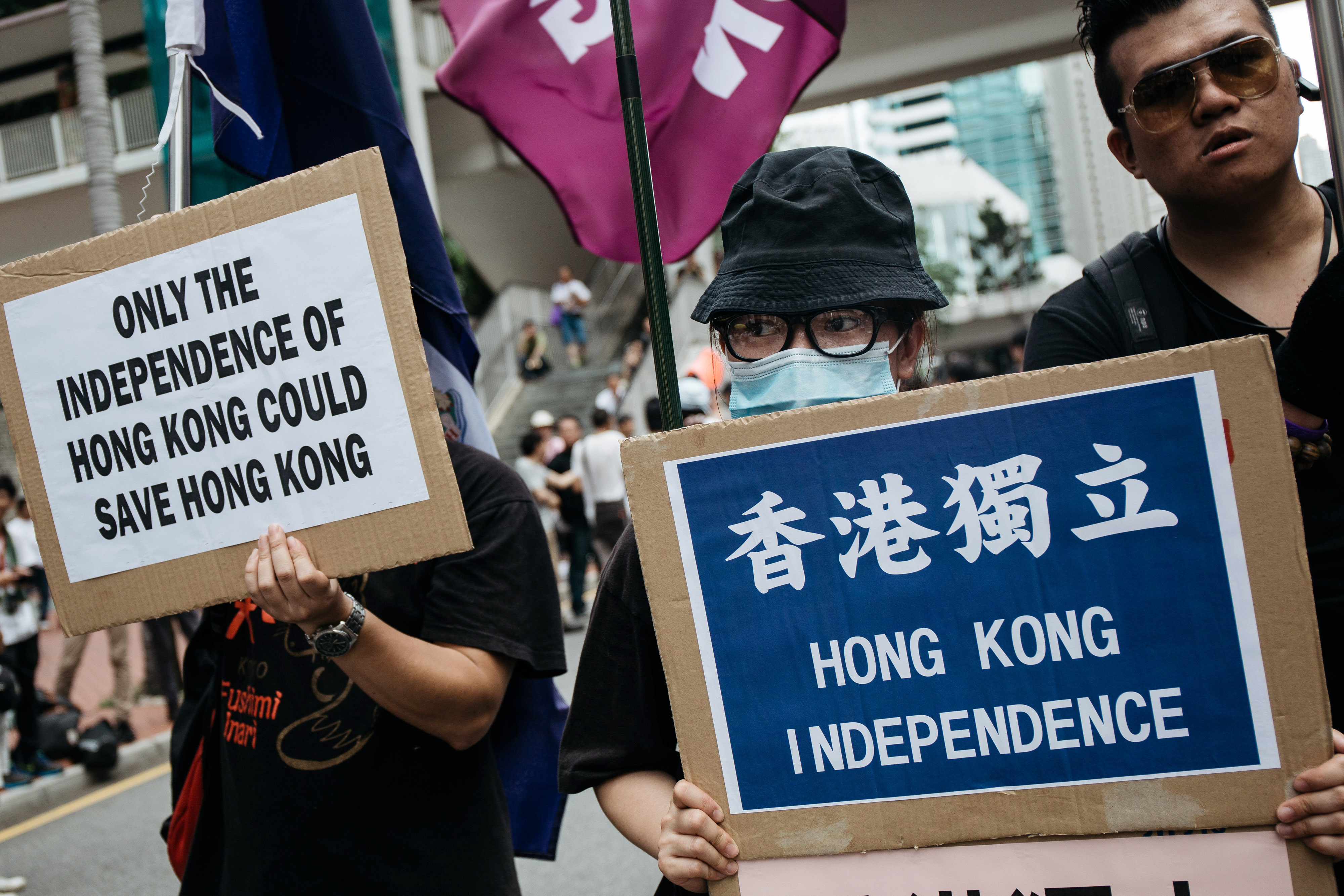 Protesters hold placards calling for Hong Kong's independence as they march on the street during a rally on July 1, 2016, in Hong Kong