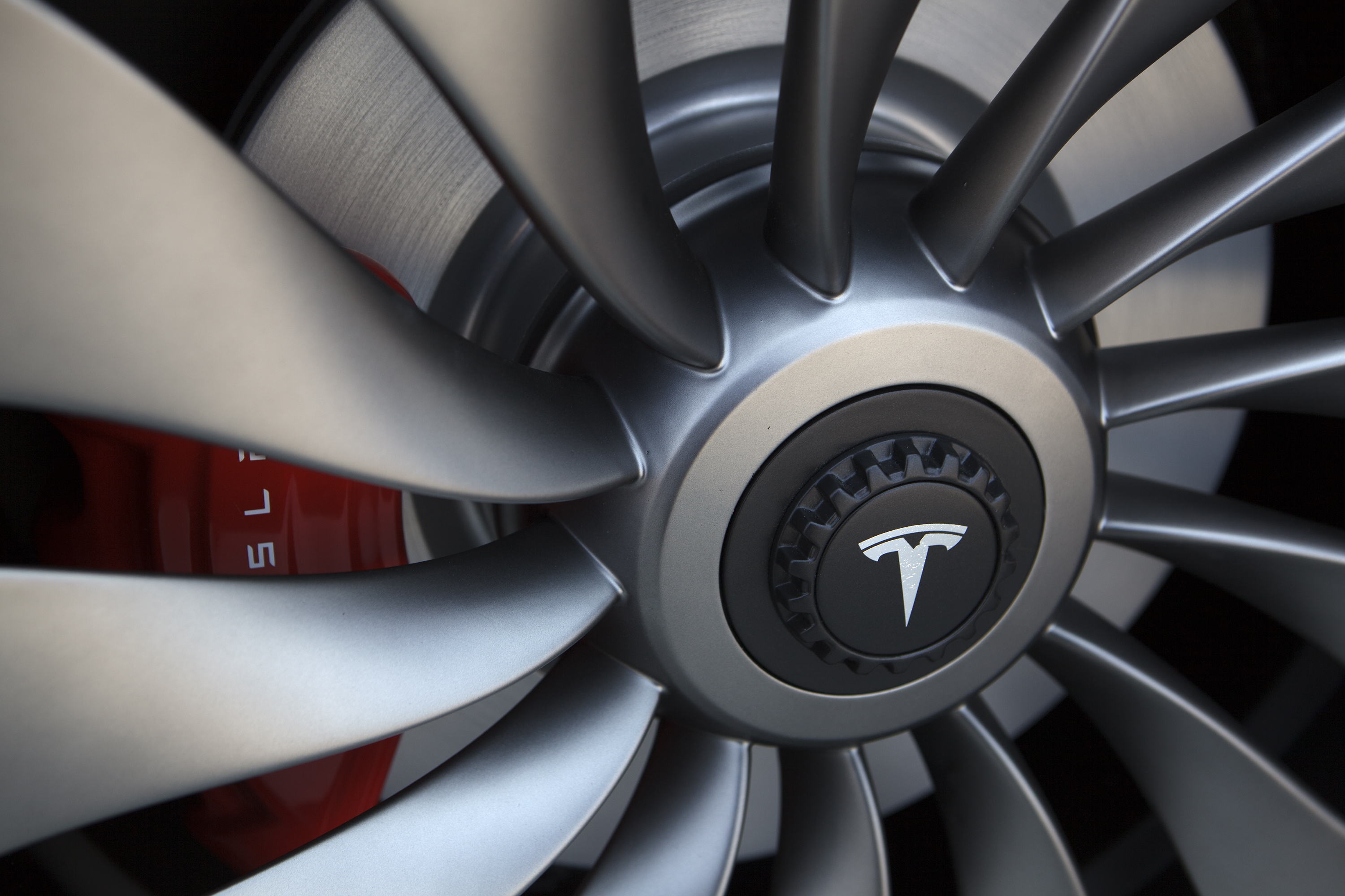A Tesla Motor Inc. logo is displayed on the wheel of a Model 3 vehicle outside the company's Gigafactory in Sparks, Nevada, U.S., on Tuesday, July 26, 2016.