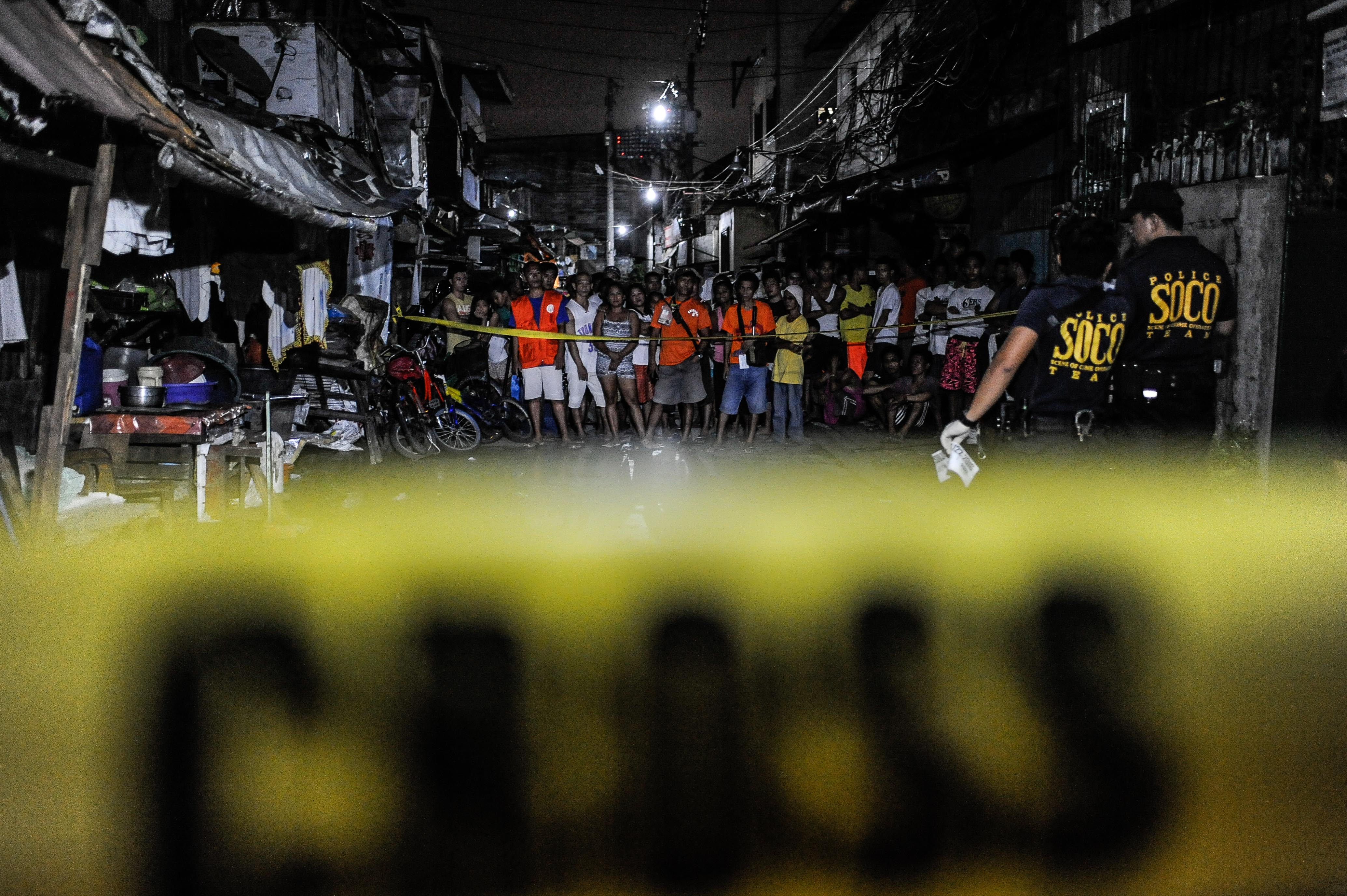 Police examine the body of an alleged drug dealer and victim of a summary execution on July 14, 2016, in Manila