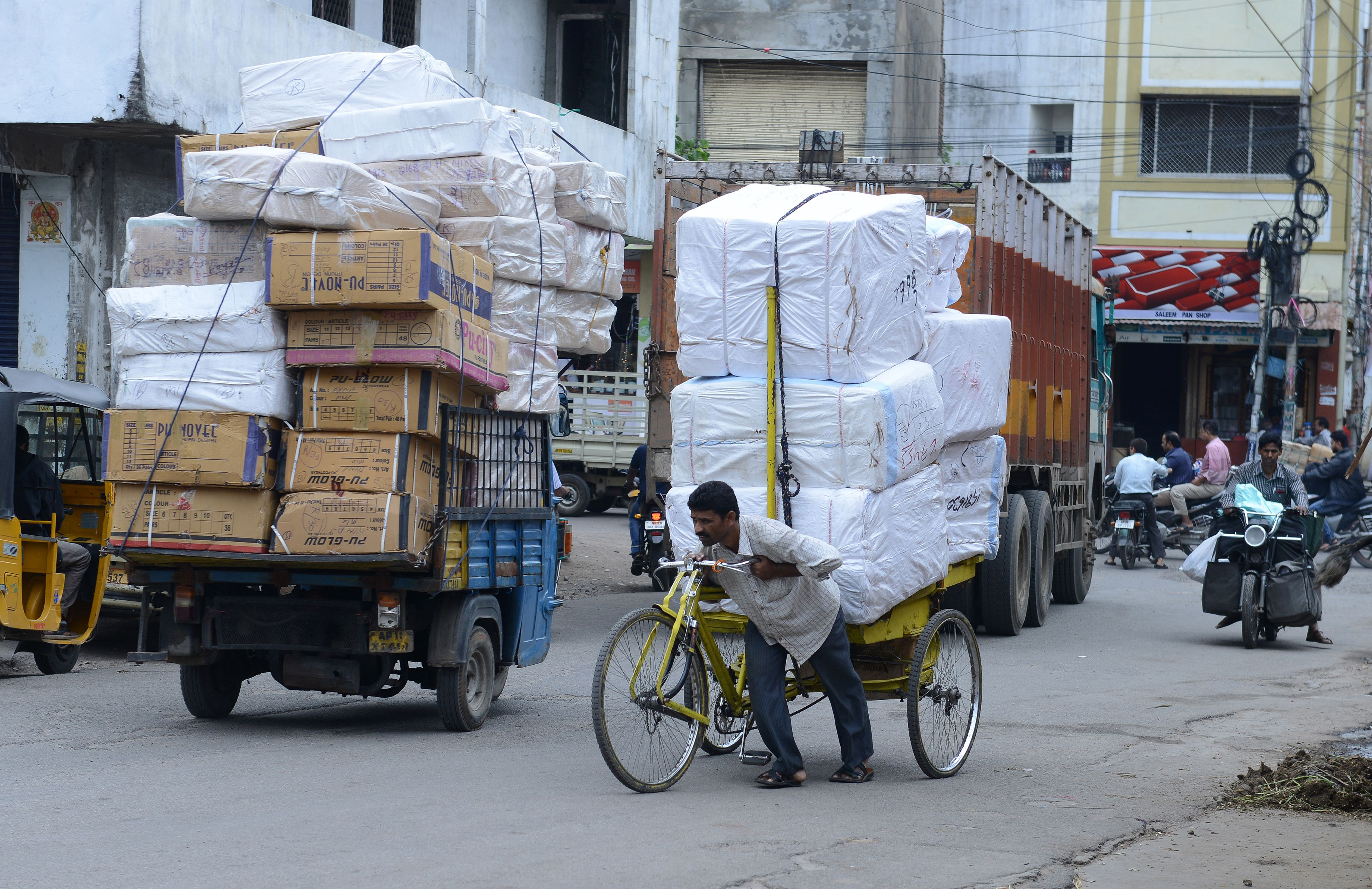 Indian labourer pushes a tri-cycle laden with consumer goods towards a wholesale shop  in Hyderabad on August 3, 2016.