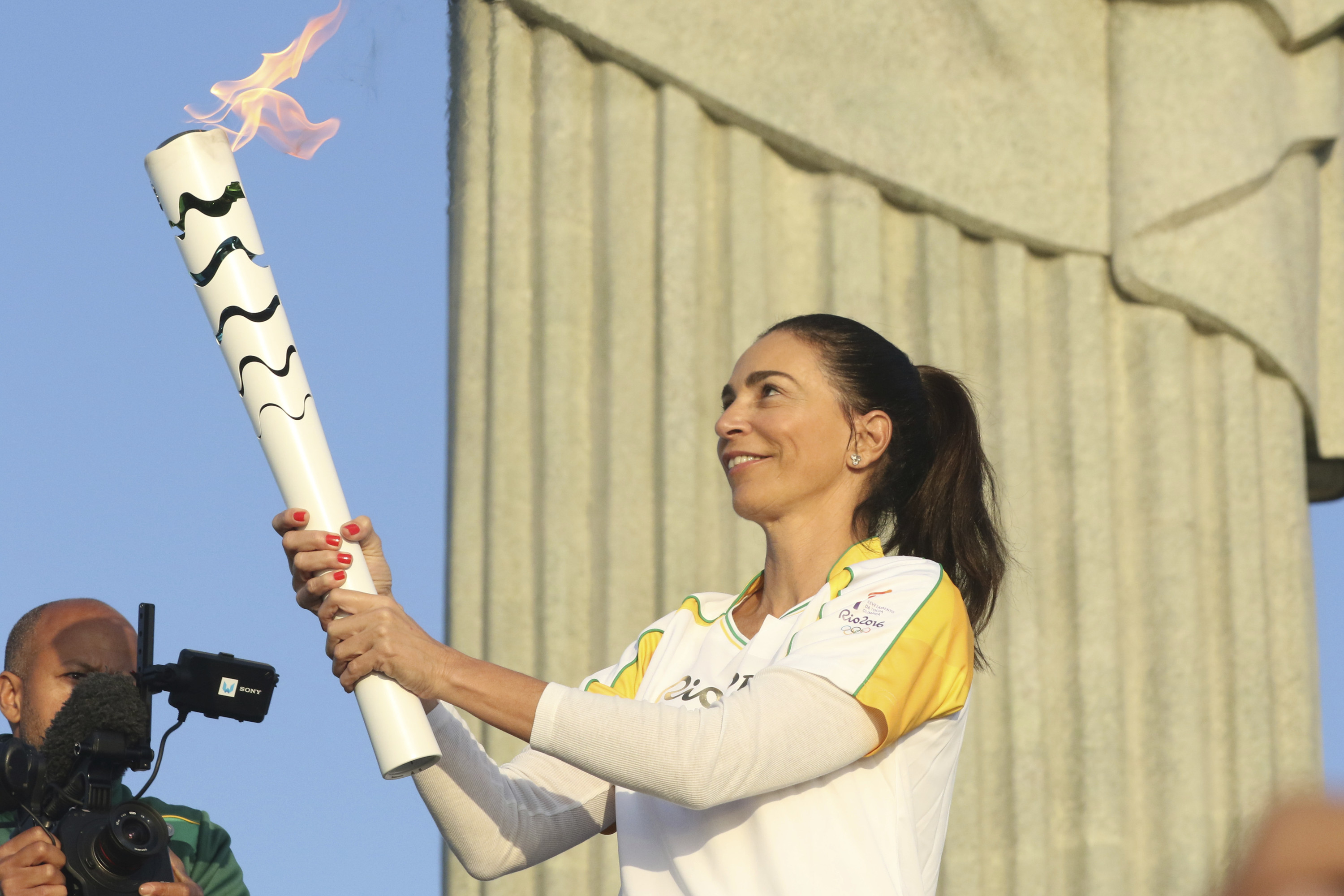 Brazilian former volleyball player Isabel holds the Olympic flame at Christ The Redeemder Momument on Aug. 5 in Rio de Janeiro.