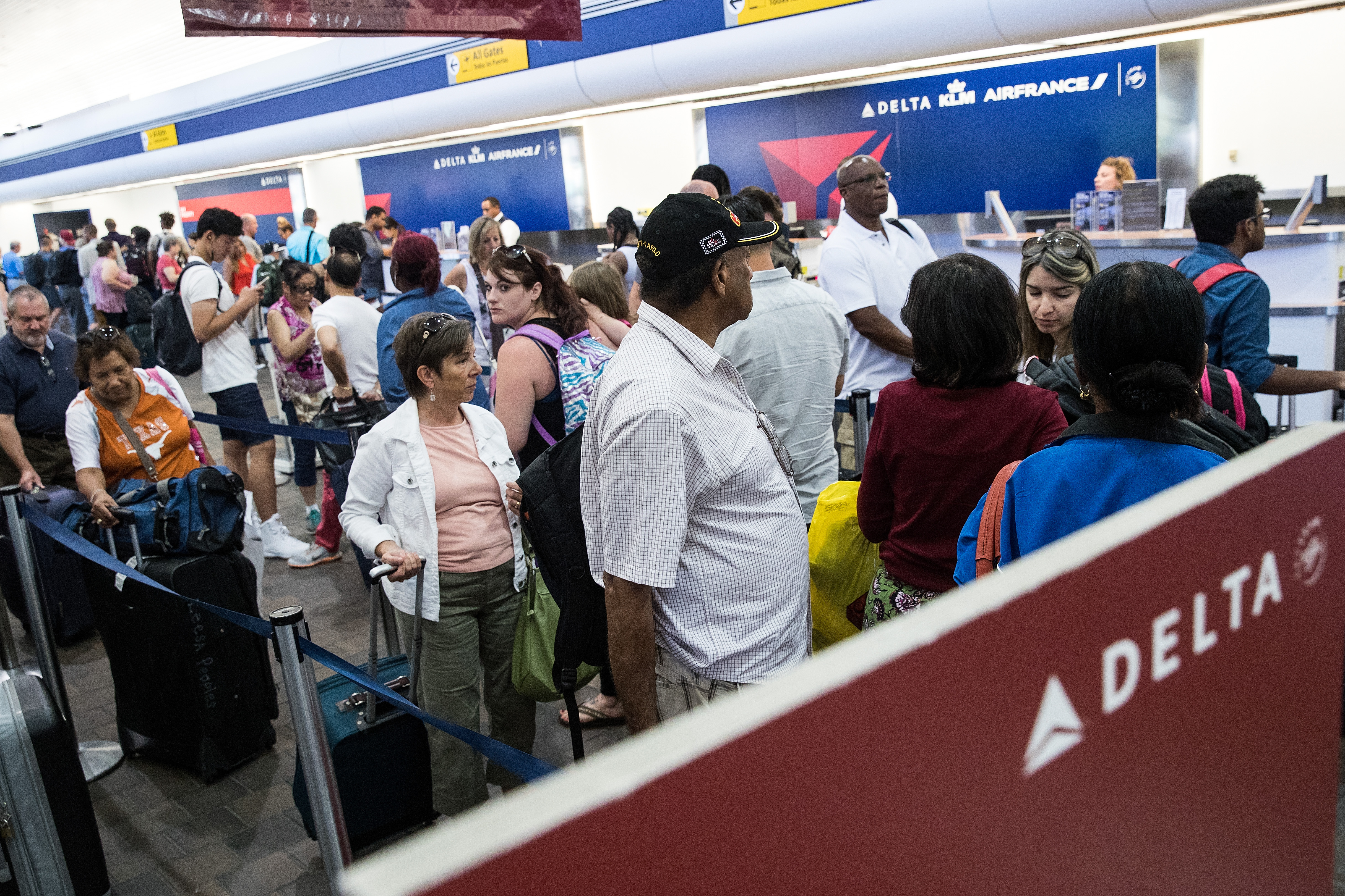 Travelers wait in line at the Delta check-in counter at LaGuardia Airport , August 8, 2016 in the Queens borough of New York City. Delta flights around the globe were grounded and delayed on Monday morning due to a system outage.