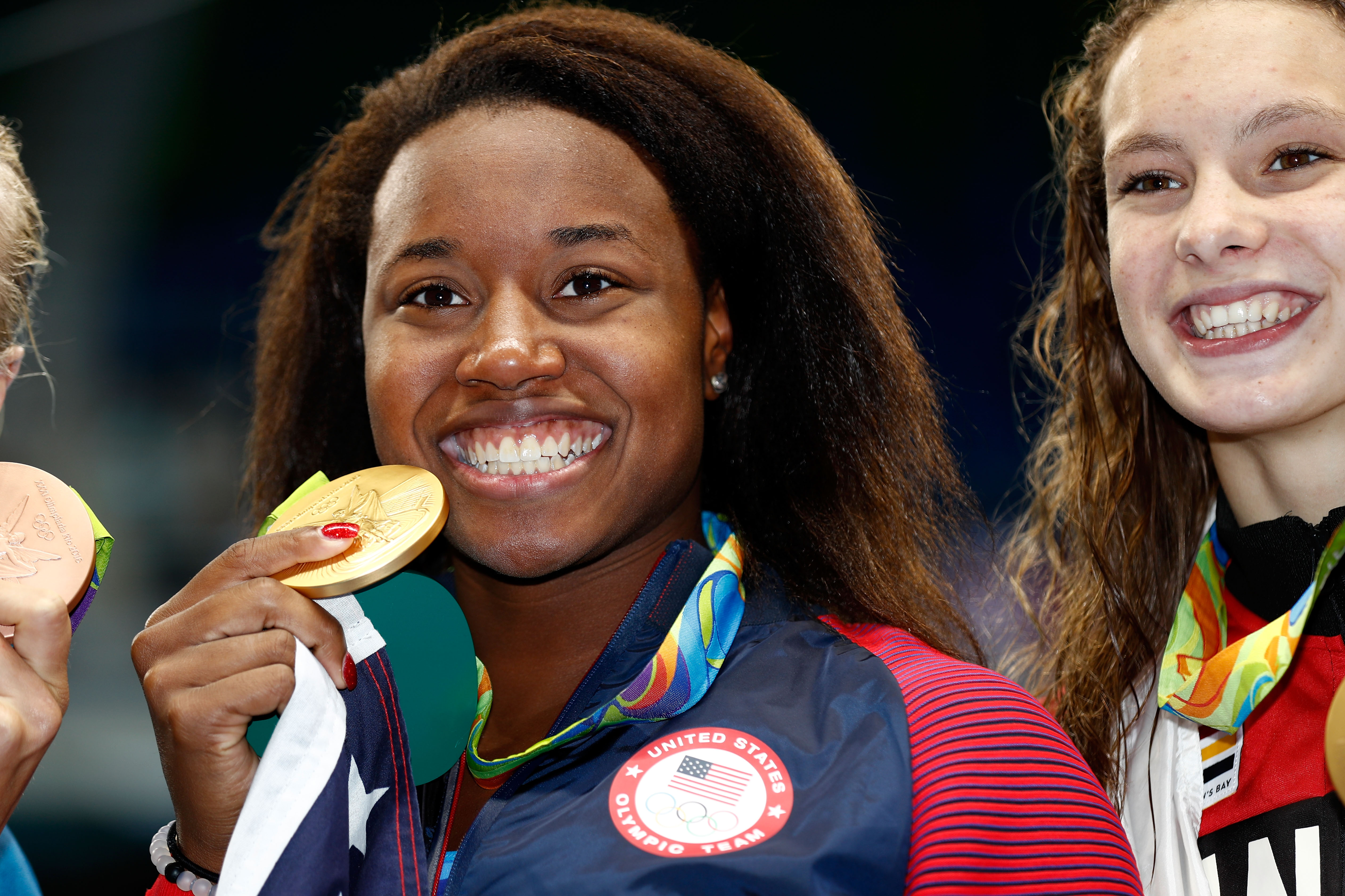 Gold medalist Simone Manuel of the United States celebrates during the medal ceremony for the Women's 100m Freestyle Final on Day 6 of the Rio 2016 Olympic Games at the Olympic Aquatics Stadium on August 11, 2016 in Rio de Janeiro, Brazil.