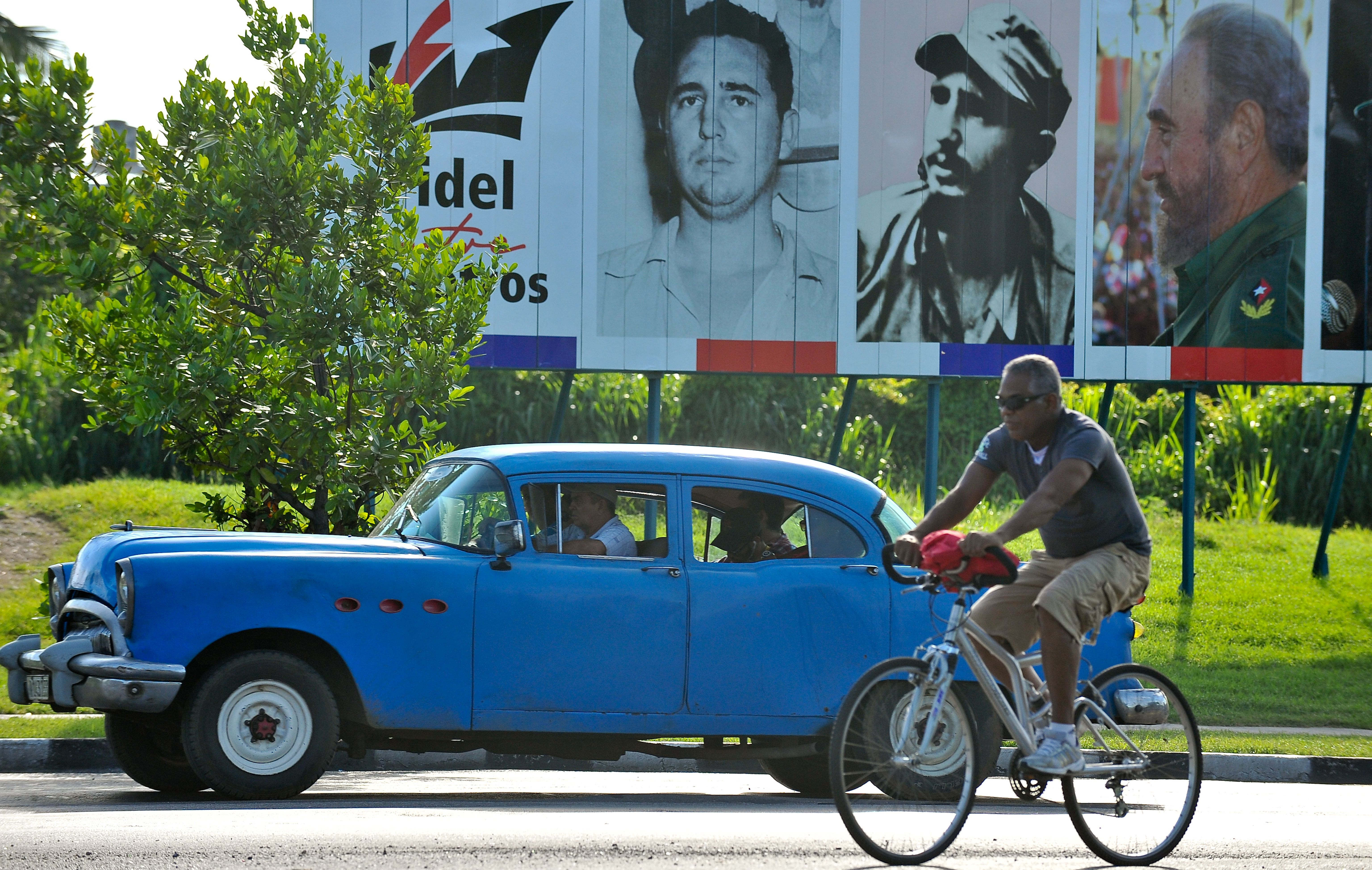 An old American car drives past a billboard of Cuban former President Fidel Castro in Havana on August 12, 2016.