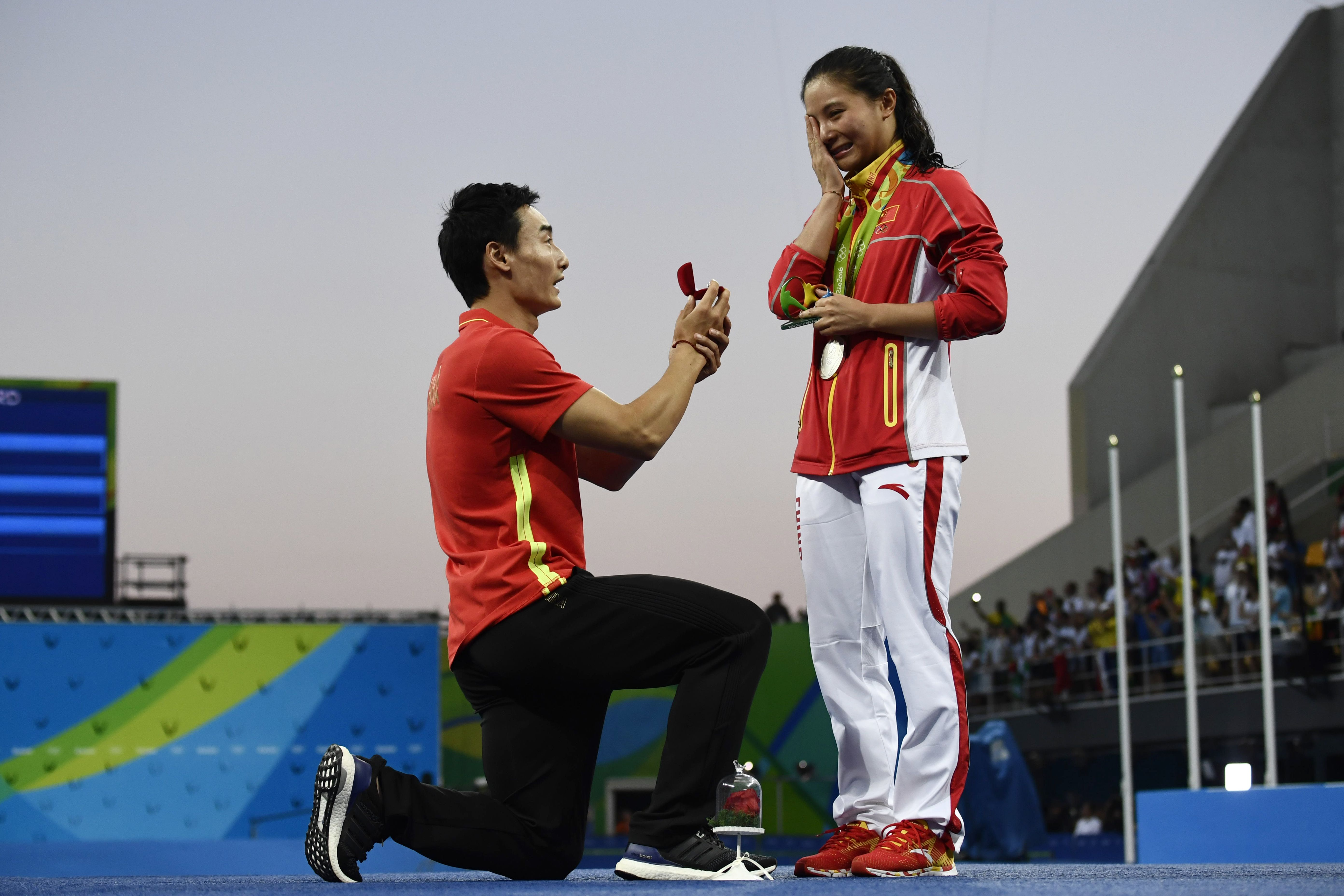 China's silver medalist He Zi, right, receives a marriage proposal from bronze medalist and fellow Chinese diver Qin Kai during the podium ceremony of the women's diving 3-m springboard final in Rio de Jainero on Aug. 14, 2016