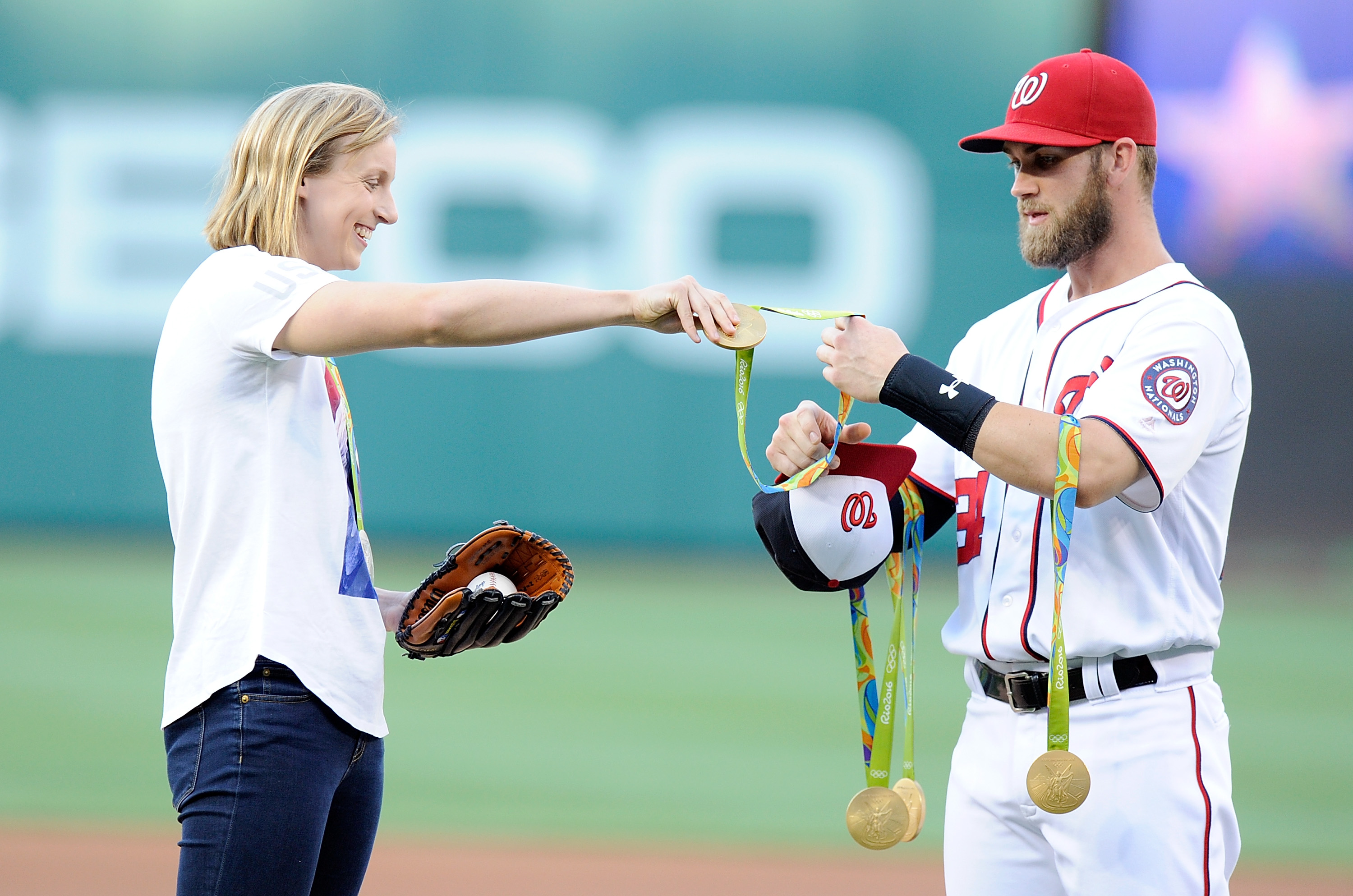 Katie Ledecky hands her Olympic medals to Bryce Harper before throwing out the opening pitch at Nationals Park on Aug. 24, 2016 in Washington, DC.
