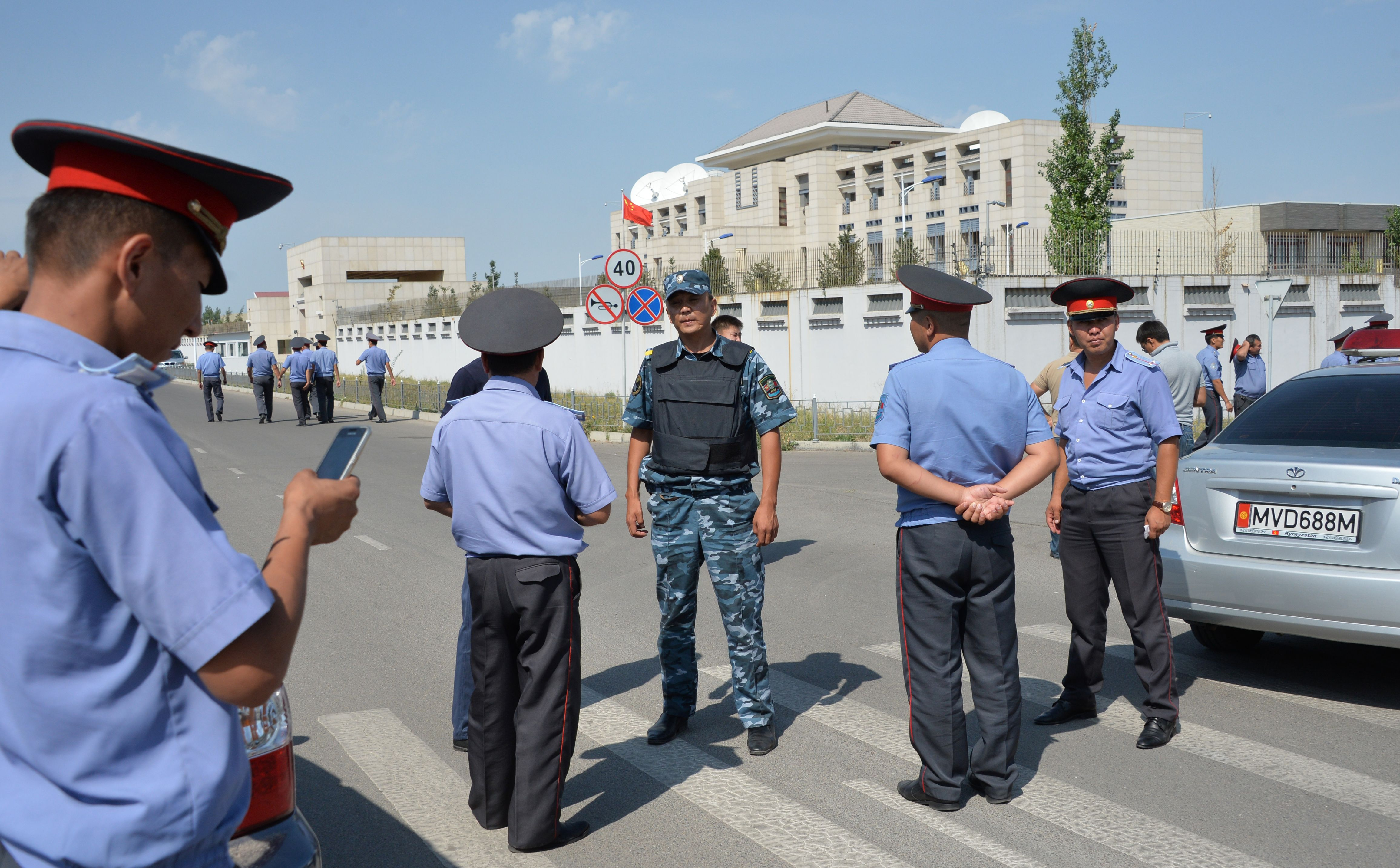 Police officers gather outside the Chinese embassy in Bishkek, Kyrgyzstan, on Aug. 30, 2016. A van driven by a suicide bomber exploded after ramming through a gate.