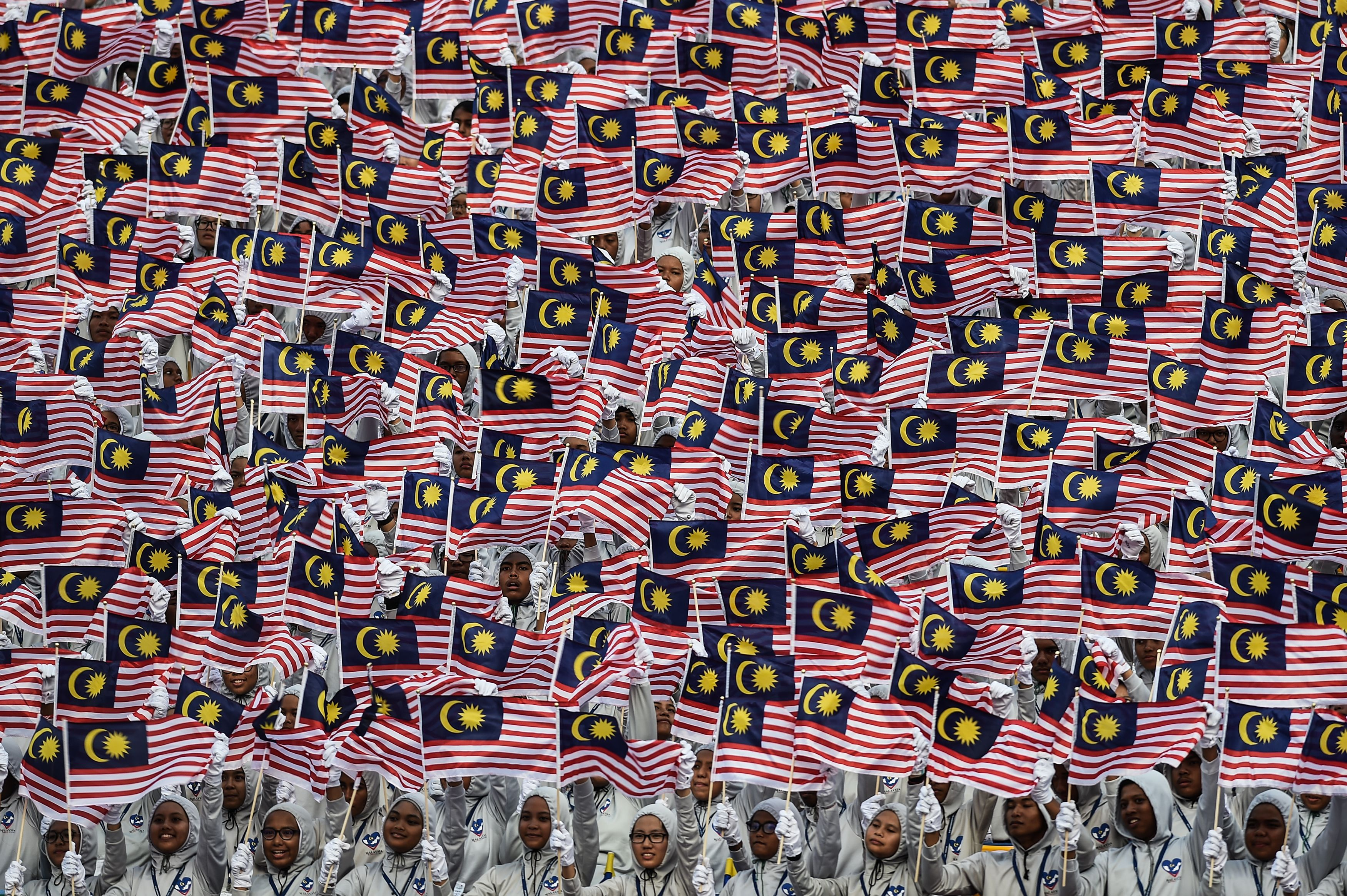 Malaysian schoolchildren wave national flags during the 59th National Day celebrations at Independence Square in Kuala Lumpur on August 31, 2016.