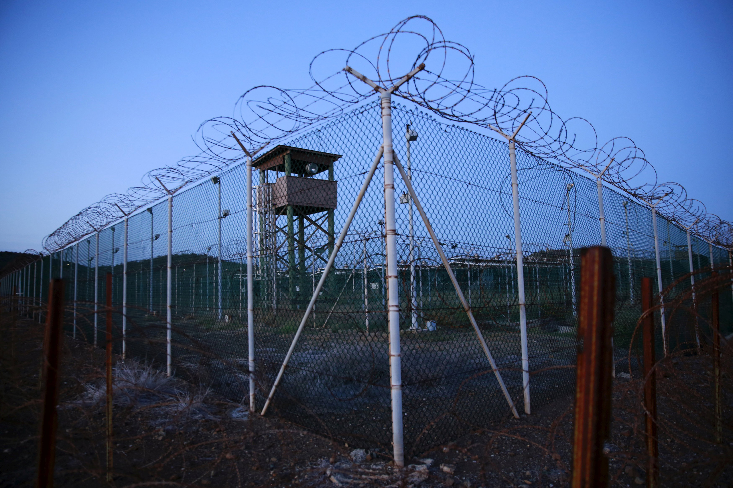 Chain-link fence and concertina wire surrounds a deserted guard tower within Joint Task Force Guantánamo's Camp Delta at the U.S. naval base in Guantánamo Bay, Cuba, on March 21, 2016