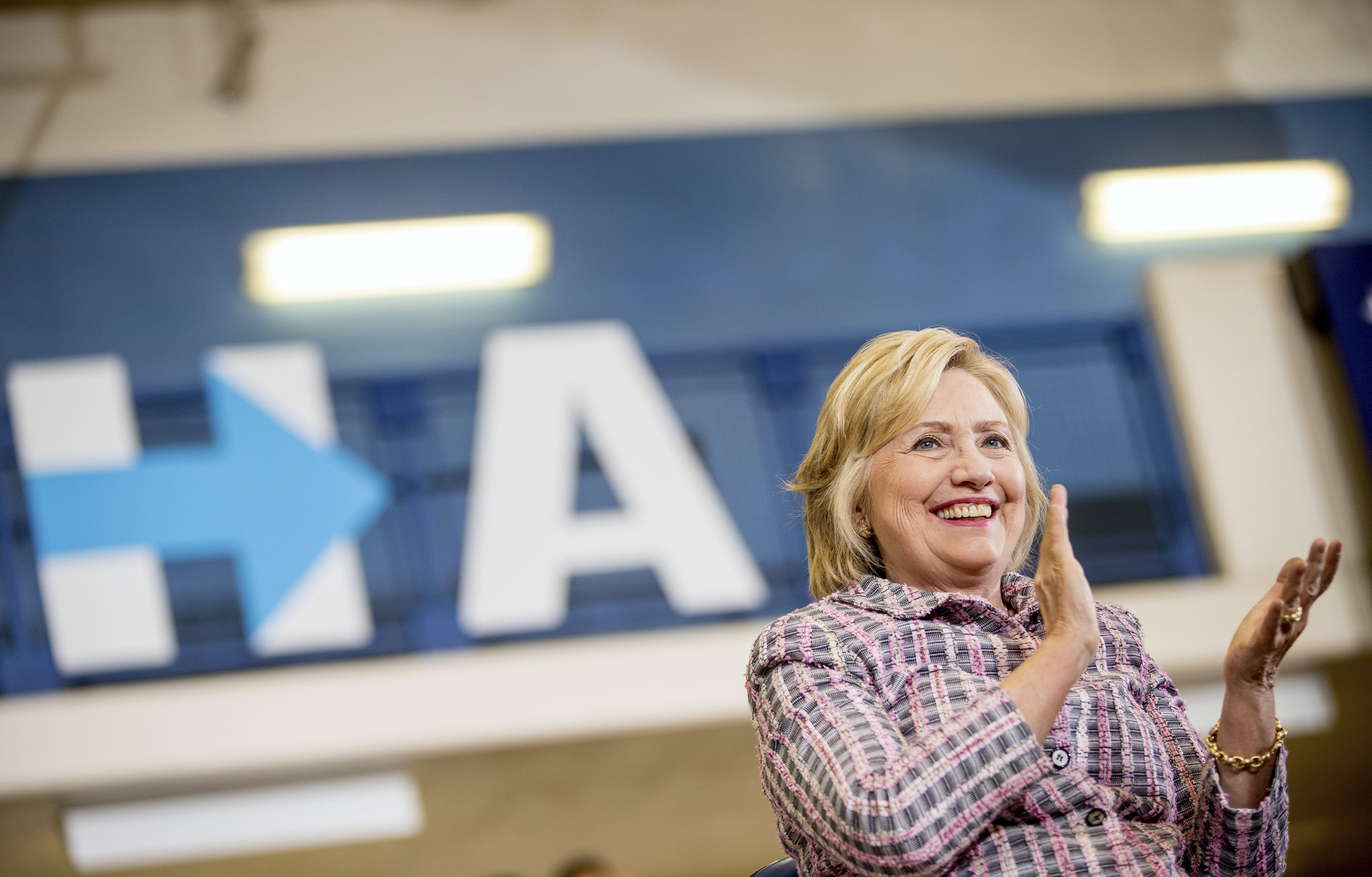 Democratic presidential candidate Hillary Clinton applauds as she sits on stage at a rally at Omaha North High Magnet School in Omaha, Neb. on Aug. 1, 2016.