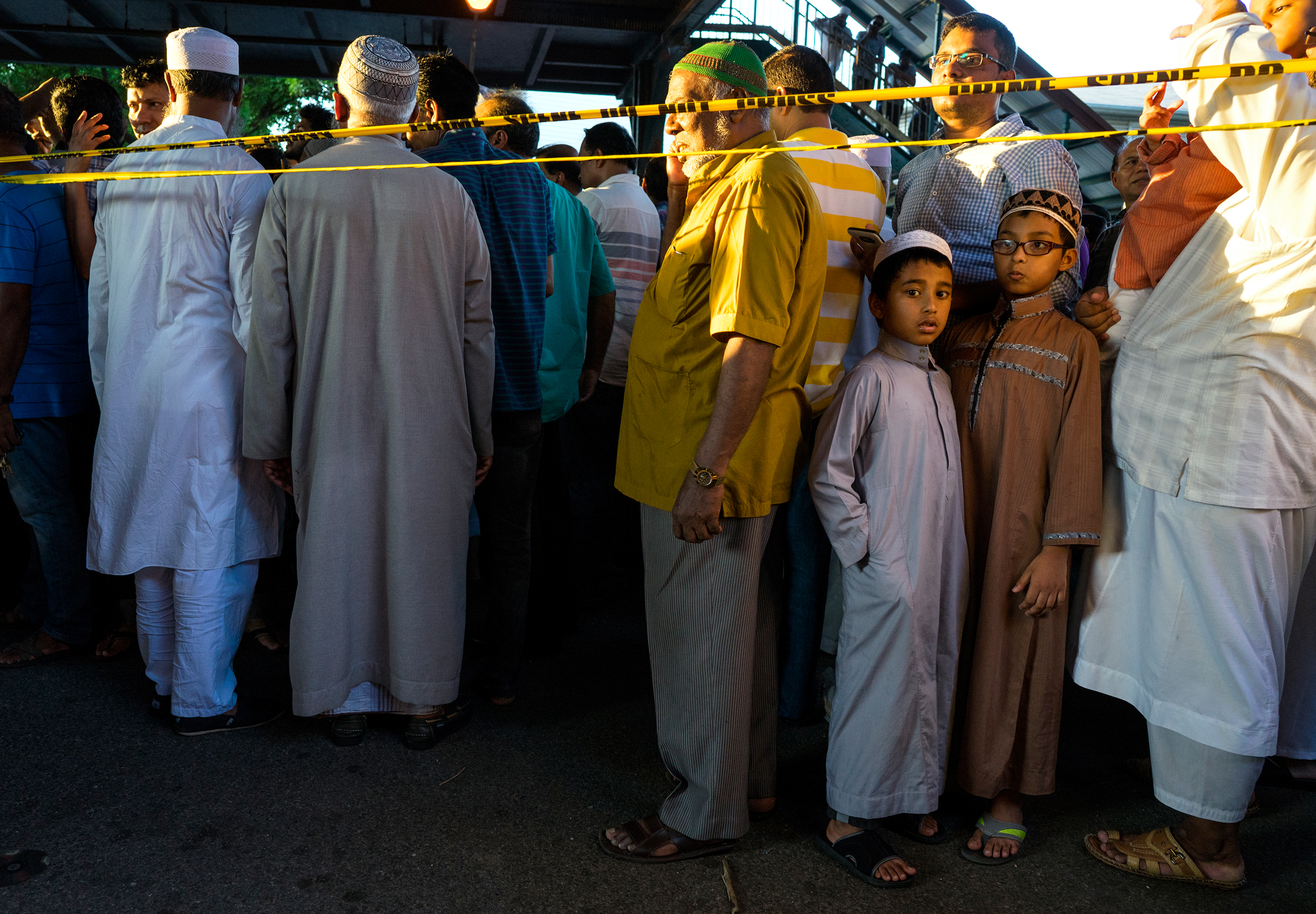 People gather for a demonstration near a crime scene where 55-year-old Imam Maulama Akonjee and his 64-year-old associate, Tharam Uddin, were shot in the back of the head left the Al-Furqan Jame Masjid mosque in the Ozone Park section of Queens in New York City on Aug. 13, 2016, .