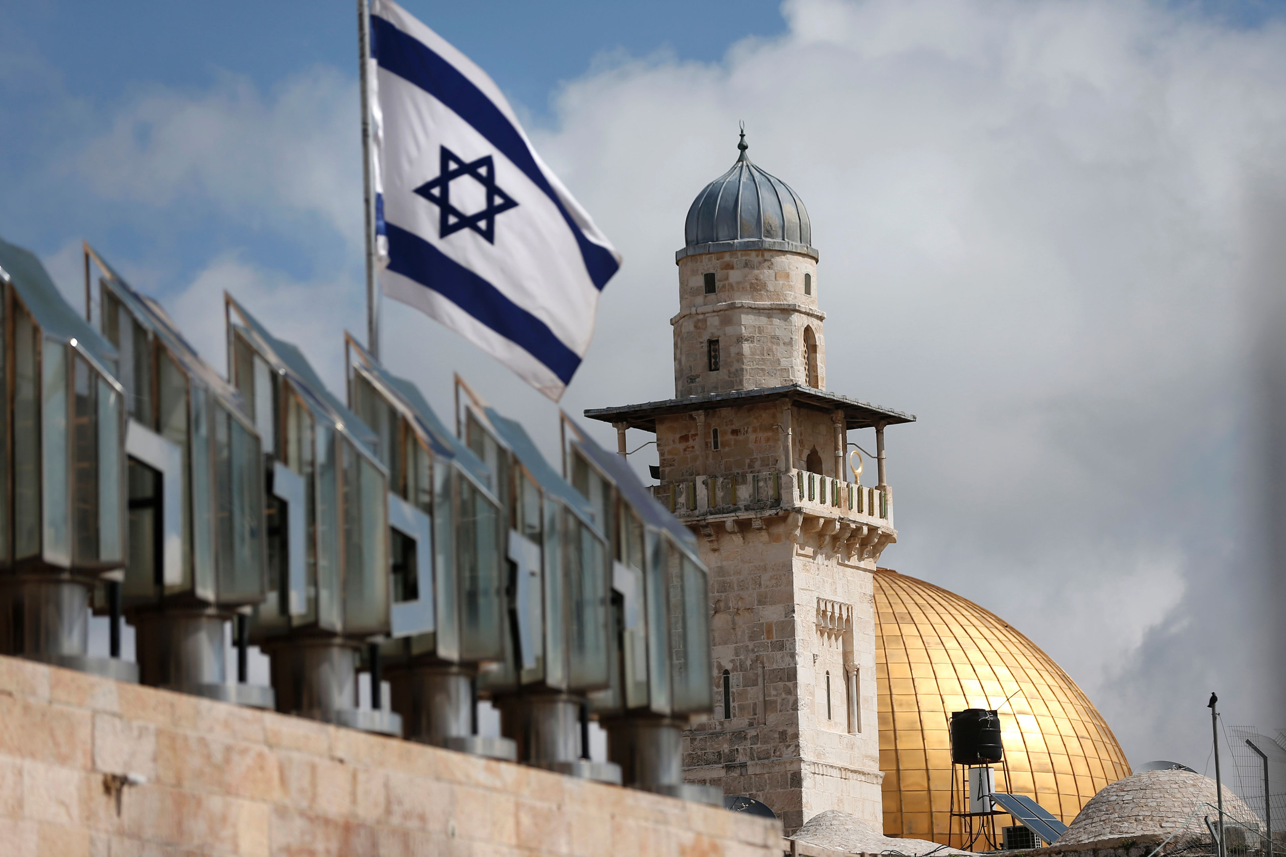 An Israeli flag is seen fleeting in front of a minaret and the Dome of the Rock on the Al-Aqsa mosque compound in Jerusalem's Old City, on March 17, 2016.