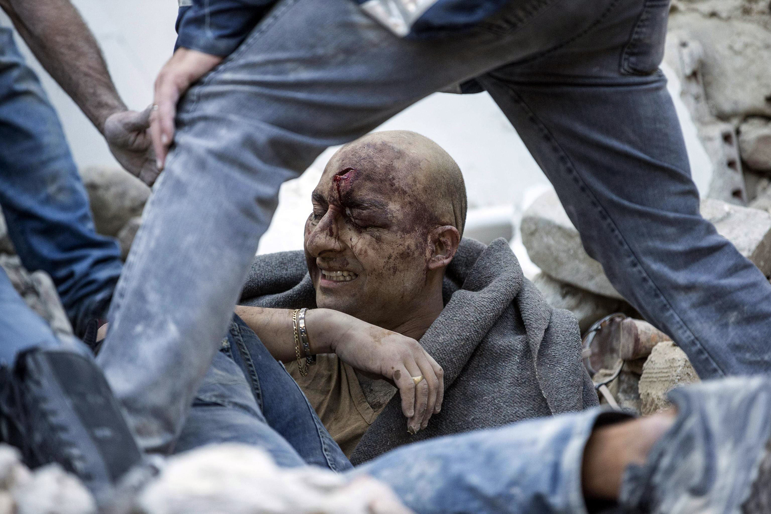 A man is pulled out of the rubble following an earthquake in Amatrice Italy, Aug. 24, 2016.