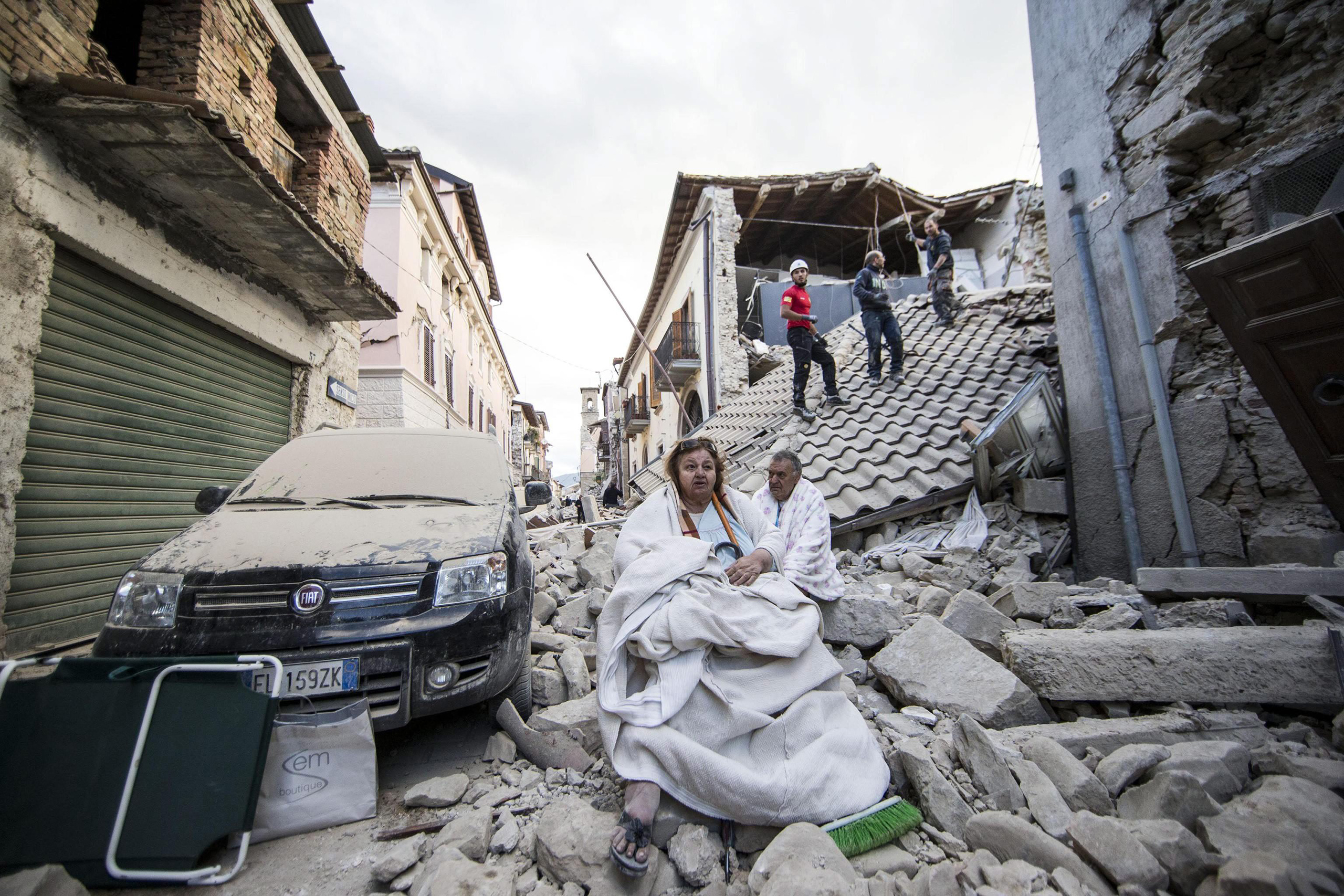 Residents look on as they stand on the rubble of collapsed buildings in Amatrice, central Italy, Aug. 24, 2016