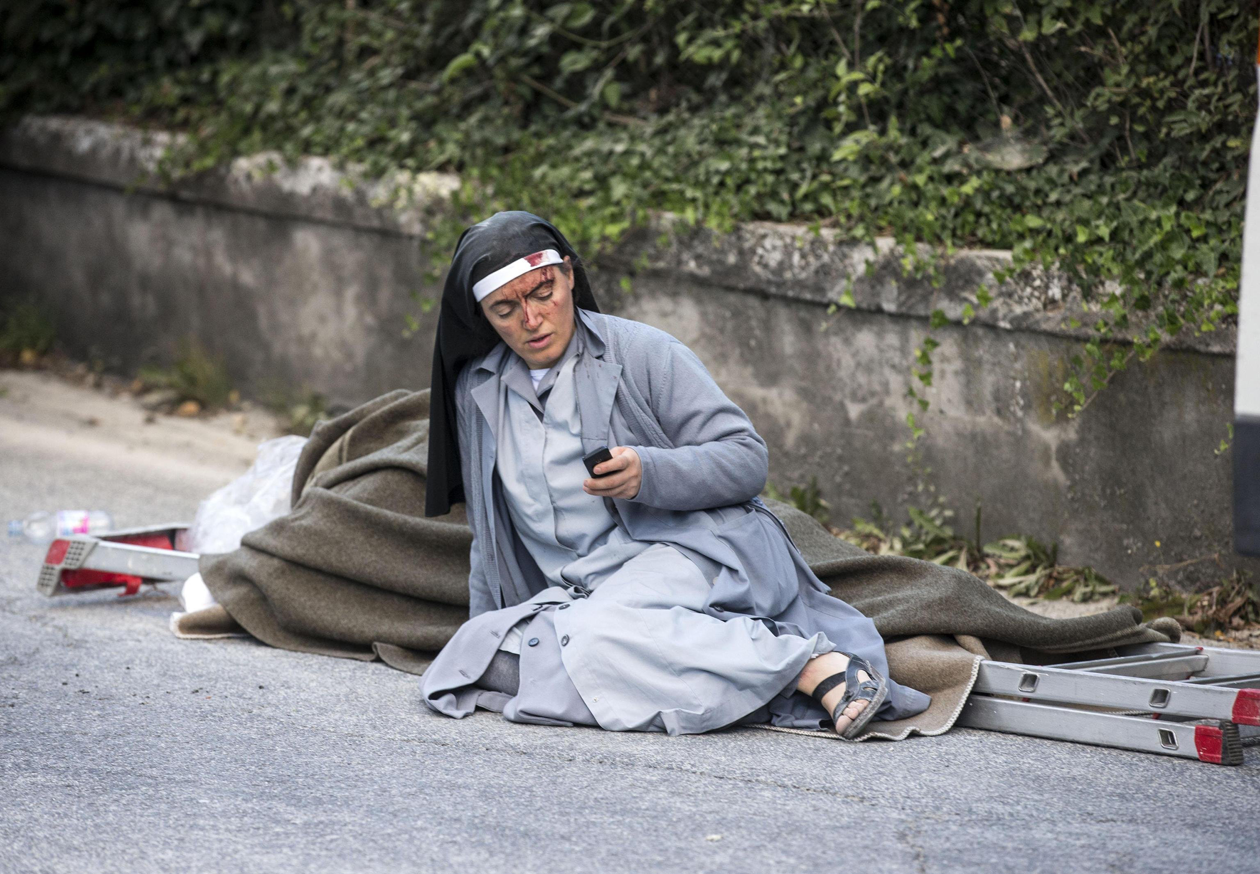A nun checks her mobile phone as she lies near a victim laid on a ladder following an earthquake in Amatrice Italy, Aug. 24, 2016.