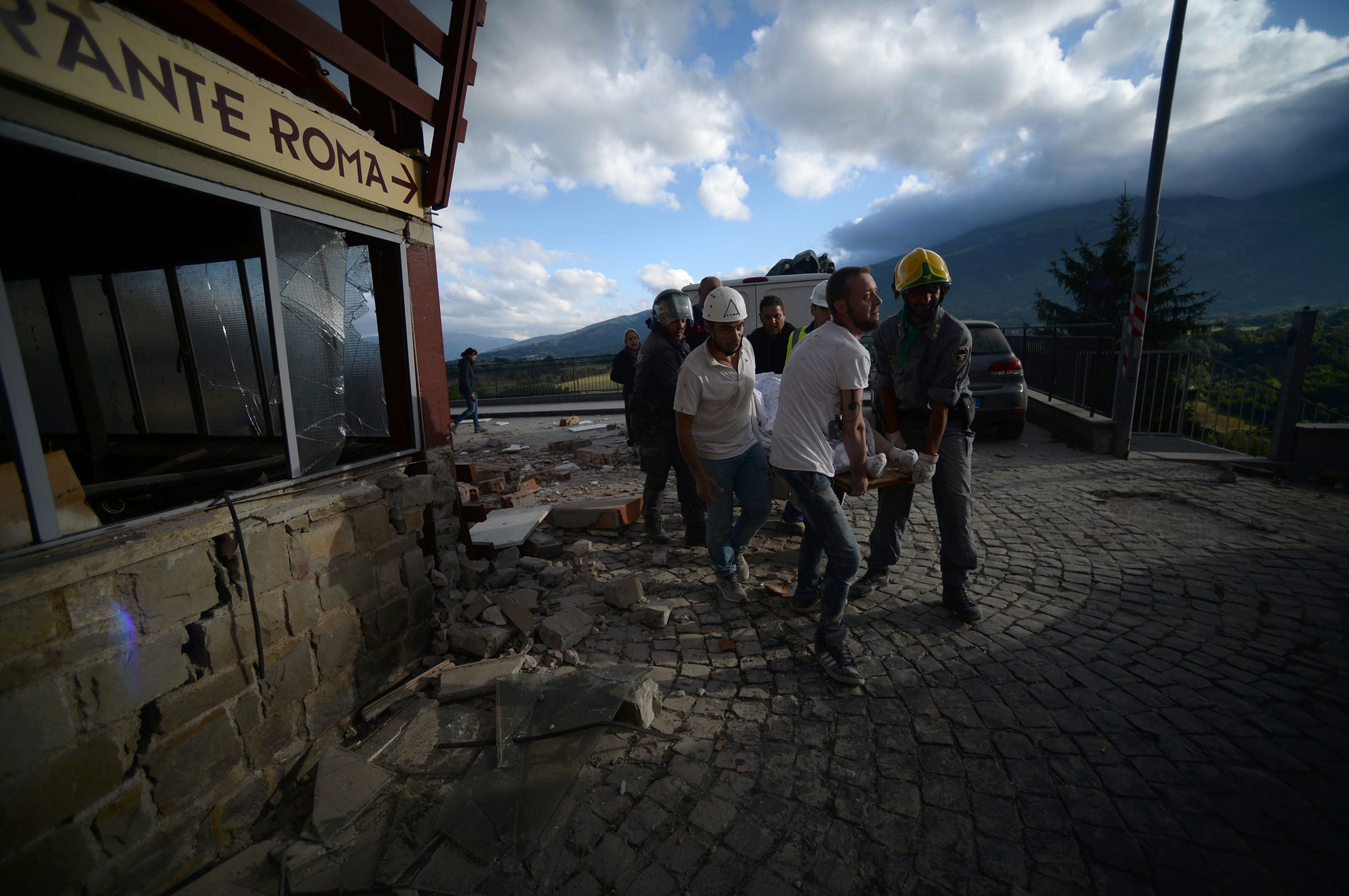 Rescuers carry a man on a stretcher in front of a damaged building after a strong earthquake hit central Italy, in Amatrice on Aug. 24, 2016.