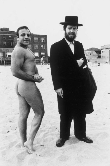 """Hassid and Jewish Bodybuilder, 1980""""The man showed up on Riis beach when there still was a nude bay and all the people started gathering around him. A nude man walks up to him and says take my picture with him becuase I am Jewish too!"""""""
