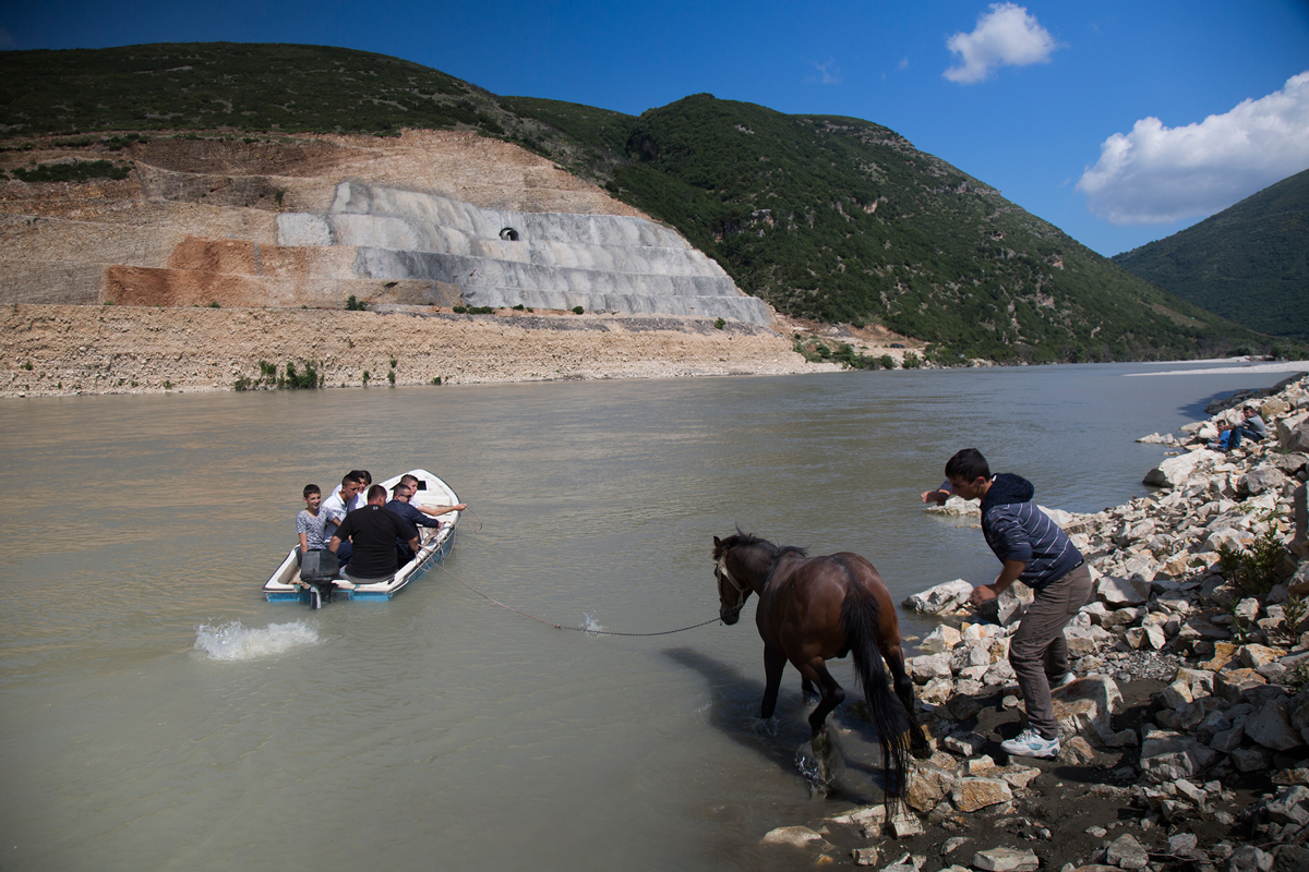 A boy slaps a horse to get it into the fast-moving waters of the Vjosa River to swim it to the other side in May 2016. The walls of the stalled Kalivac dam rise in the background, cut into the living rock of the surrounding hills.