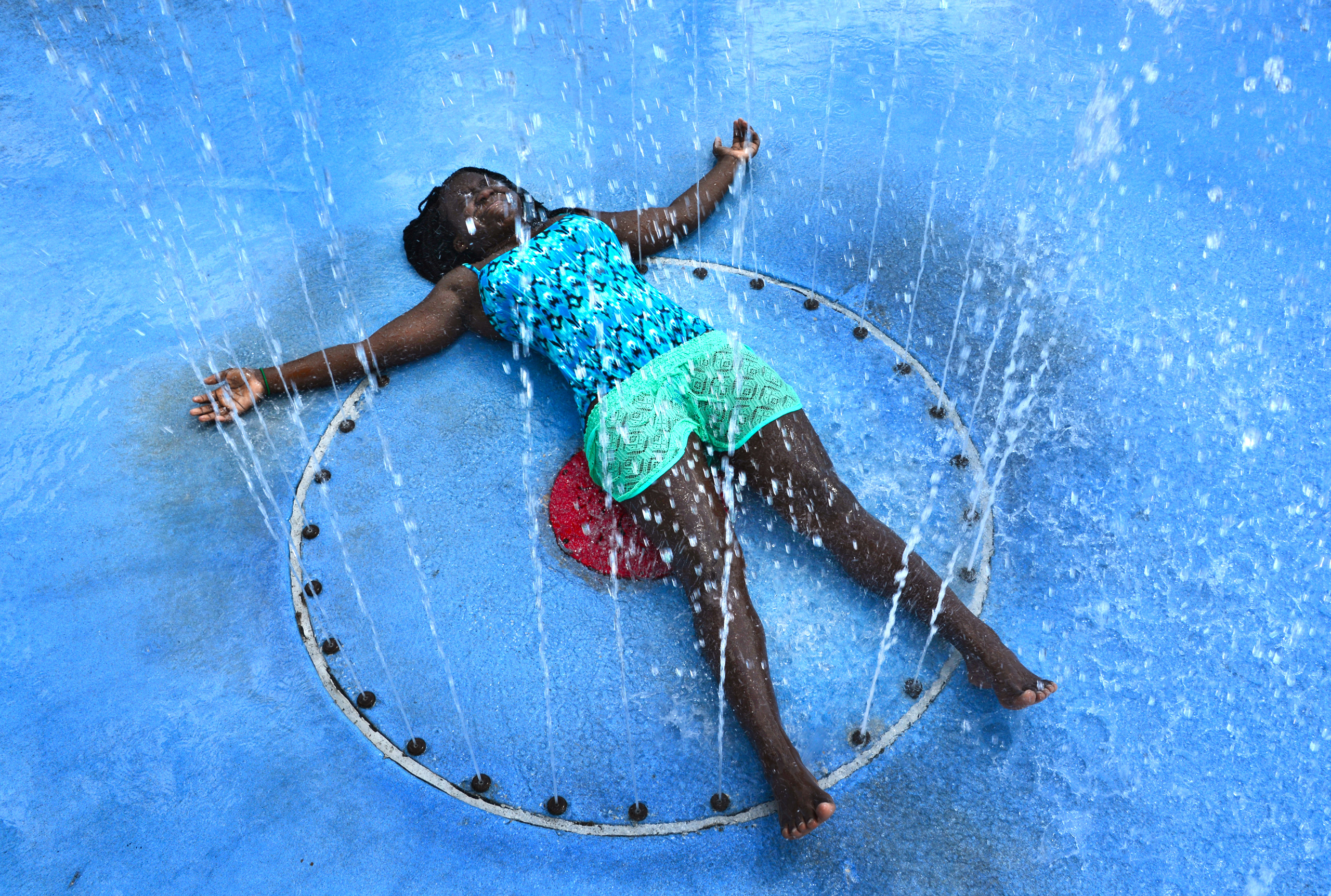 With the temperature in the mid 90's, Carliya Dove, 12, soaks up the full effects of the play fountain in Julius Guinyard Park to beat the afternoon heat in Jacksonville, Fla., on July 20, 2016.