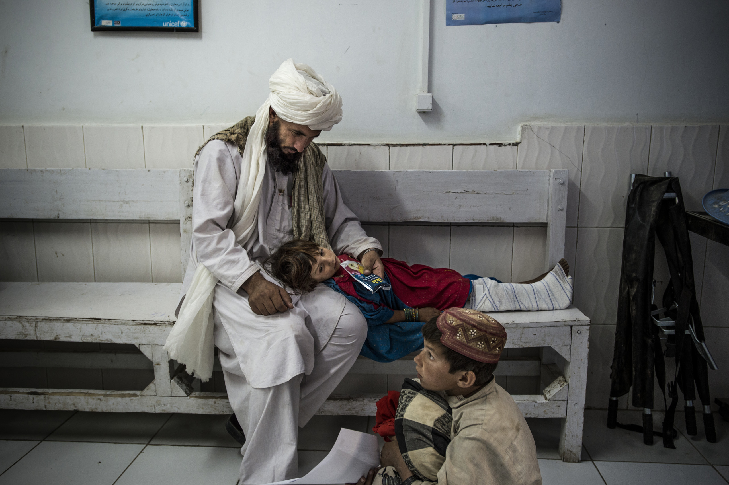 5-year-old Rona, who has a broken leg, sits next to her father Haj Bgul and brother  in the emergency room at the Boost hospital run by Doctors Without Borders, Lashkar Gah, Helmand, Afghanistan,  June 2016