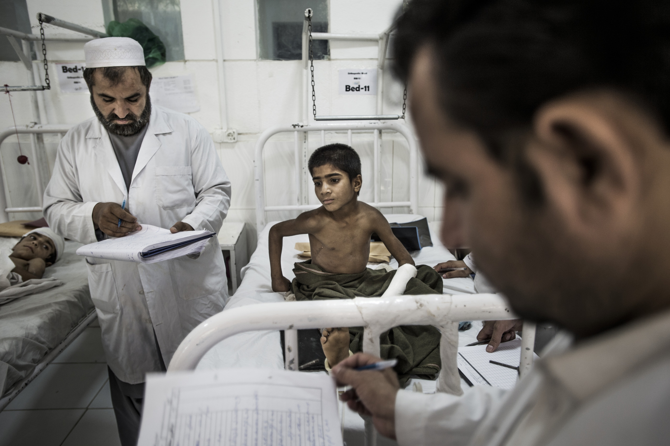 12-year-old Abdul Wali  is examined in the orthopedic ward in Boost hospital, which is run by Doctors Without Borders, Lashkar Gah, Helman, Afghanistan, June 2016.