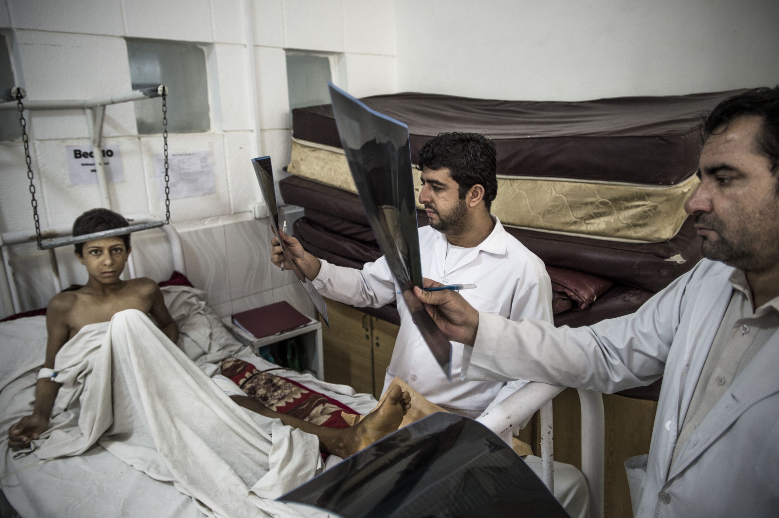 Nissan is examined in the orthopedic ward by a surgeon, Dr. Mohammadin Narriwal, in a hospital run by Doctors Without Borders, Lashkar Gah, Helmand, Afghanistan, June 2016.