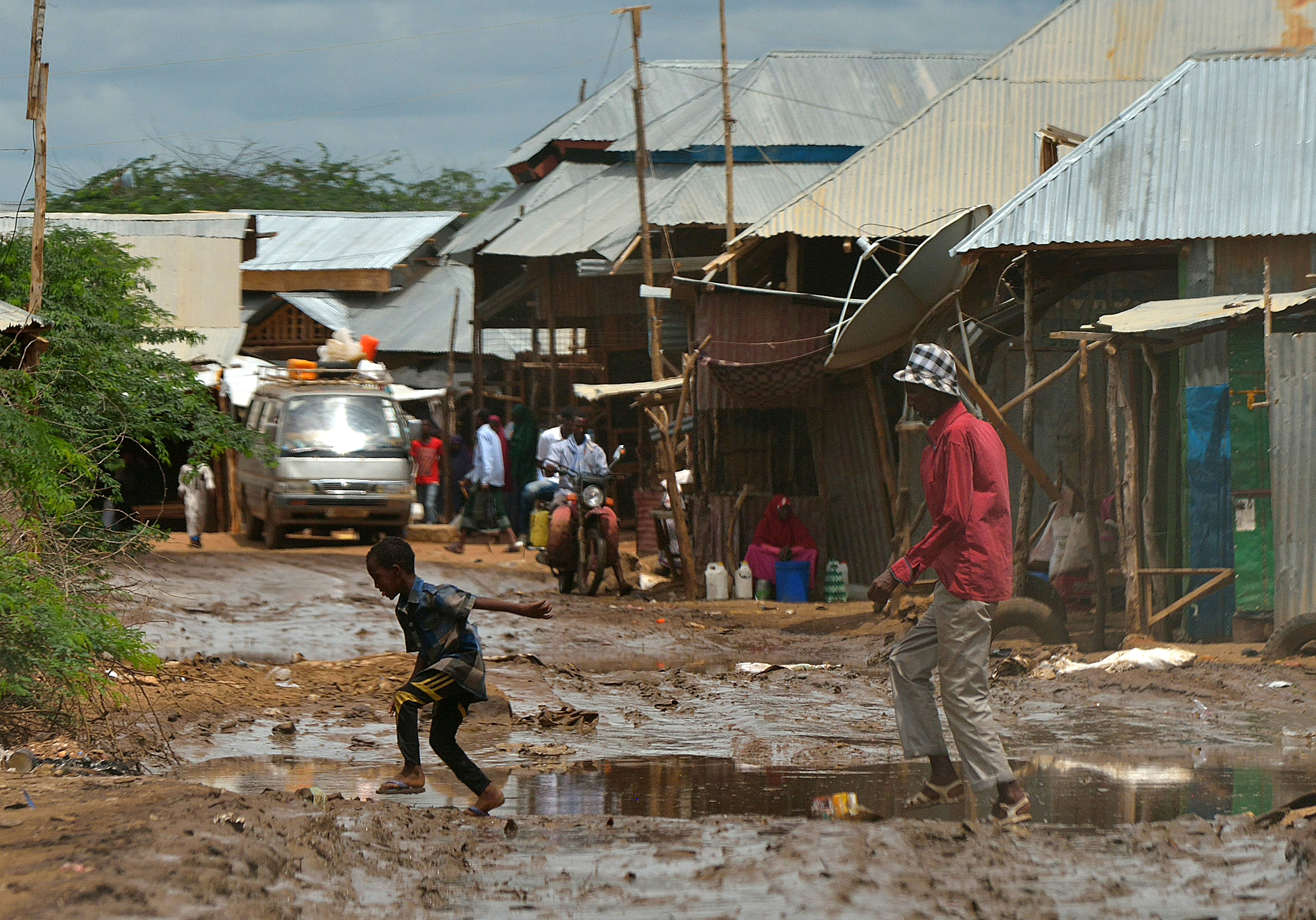People cross a muddy street at the market at IFO main camp of the Dadaab refugee camp, north of the Kenyan capital Nairobi, on April 28, 2015.  AFP PHOTO/Tony KARUMBA        (Photo credit should read TONY KARUMBA/AFP/Getty Images)