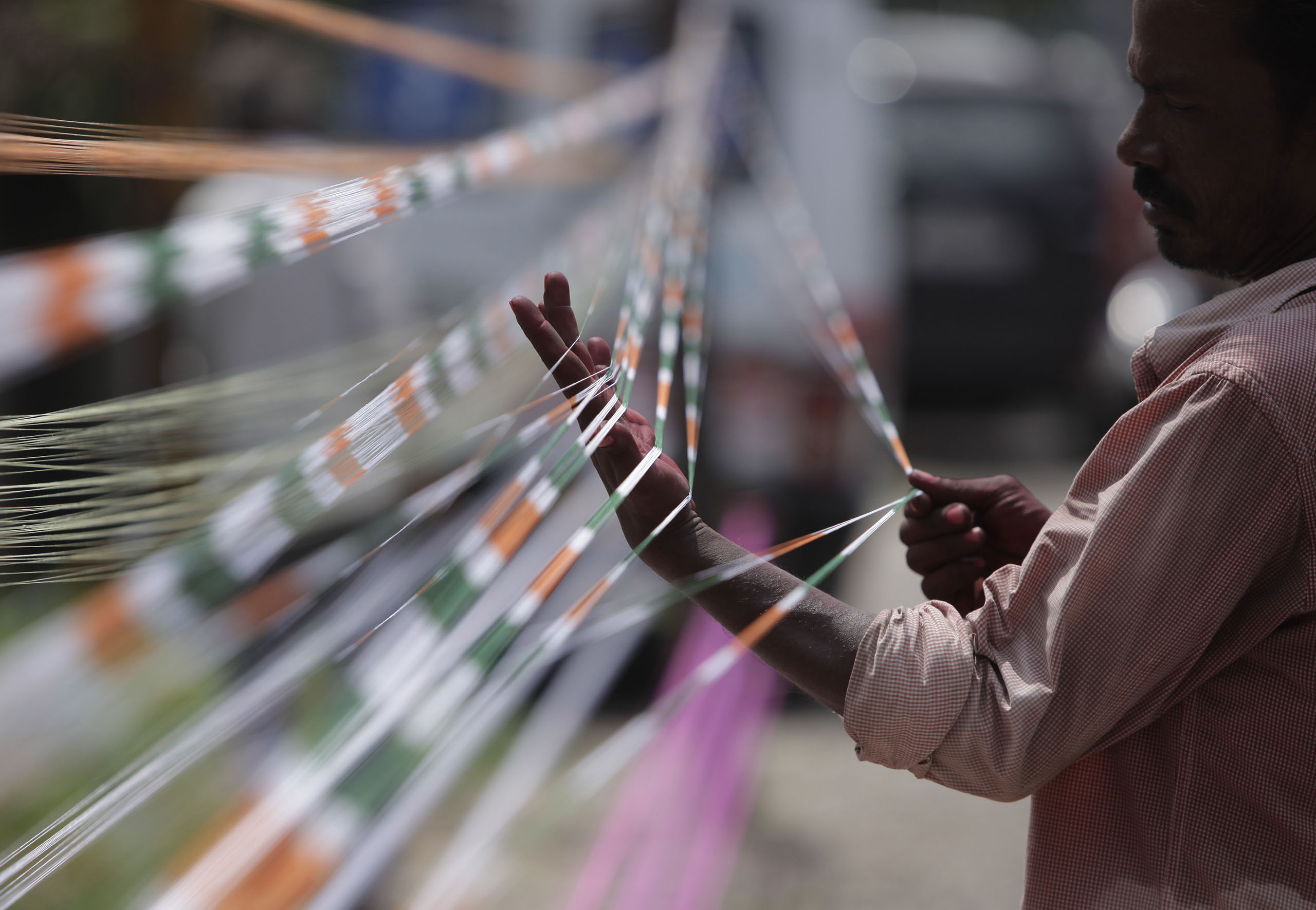 A professional thread maker prepares threads with the three colors of the Indian flag for flying kites in Jammu, India, Aug.13, 2016.