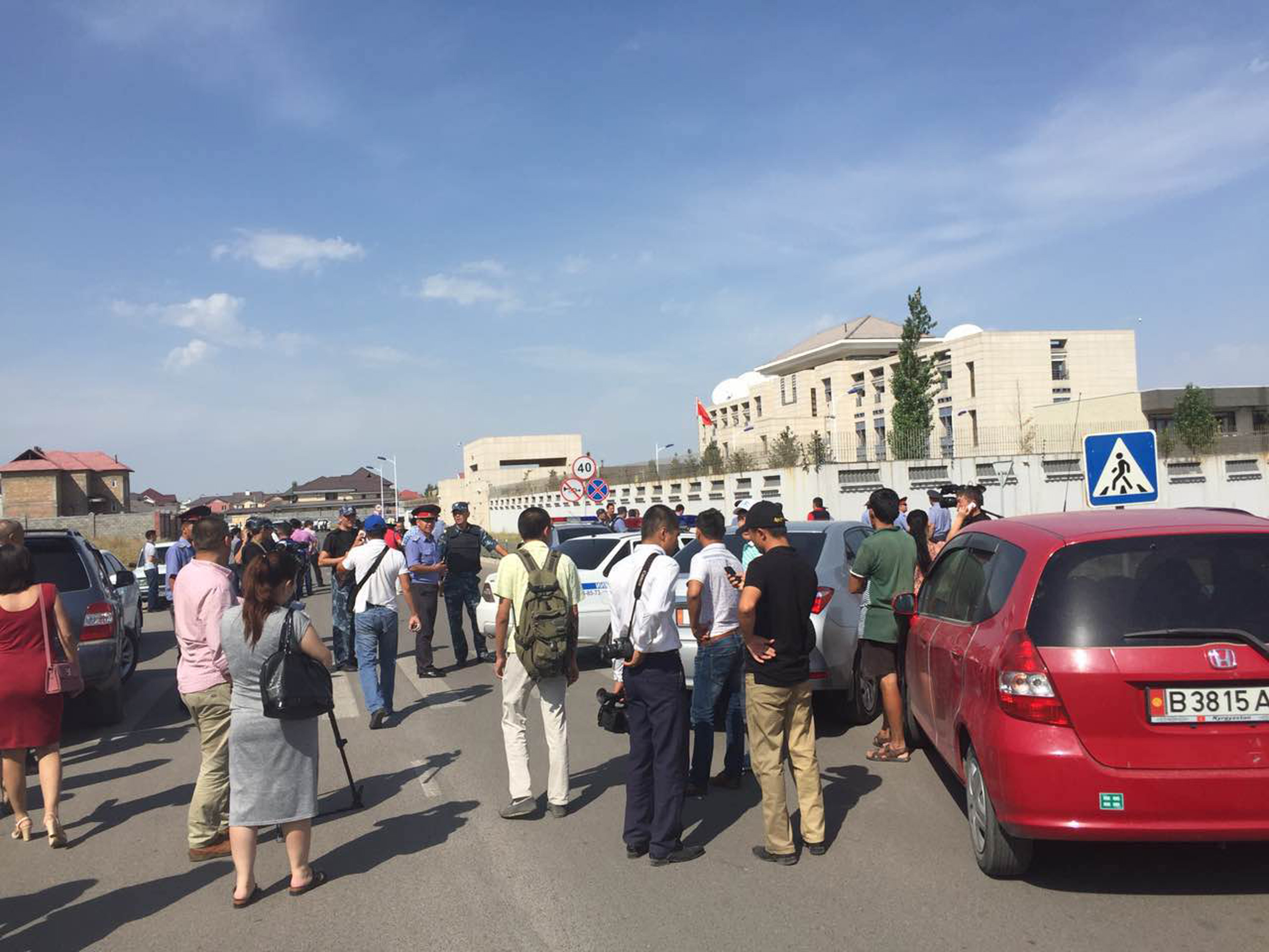In this photo released by China's Xinhua News Agency, people gather near the site of an explosion in Bishkek, Kyrgyzstan, Tuesday, Aug. 30, 2016. Kyrgyzstan's deputy prime minister says a suicide bomber rammed his car into the gate of the Chinese embassy compound in the capital Bishkek, detonating a bomb and injuring three embassy employees.