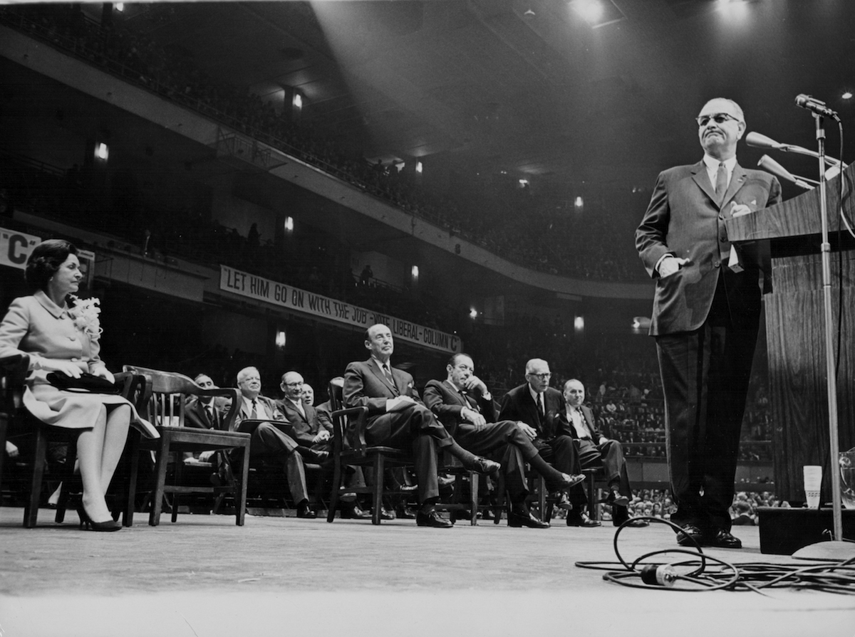 President Lyndon B Johnson addressing a rally, with his wife Lady Bird Johnson seated behind him, Madison Square Garden, New York, Oct. 21, 1964.