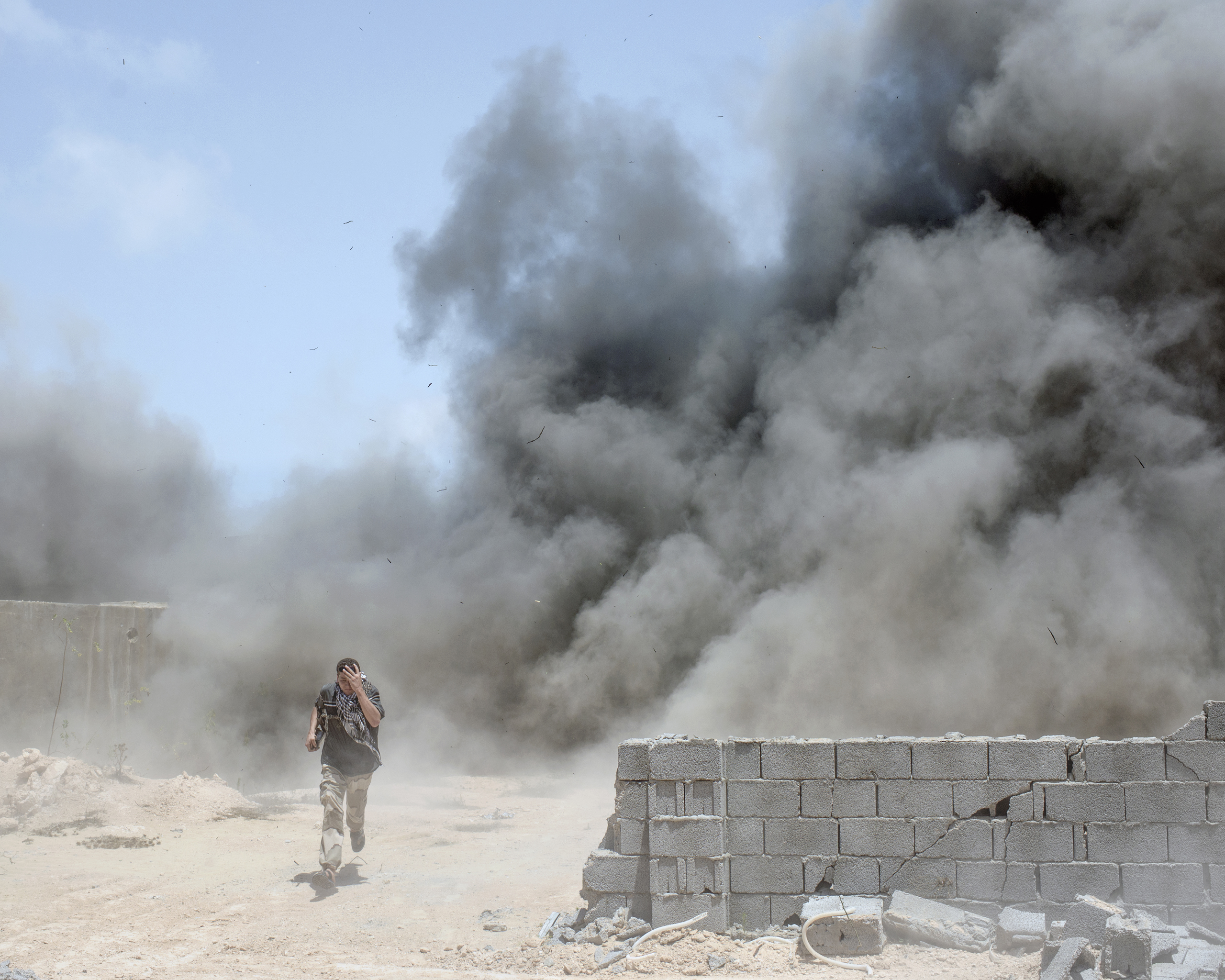 A Libyan fighter runs from a landmine explosion which injured three of his comrades, Sirt, Libya, July 2016