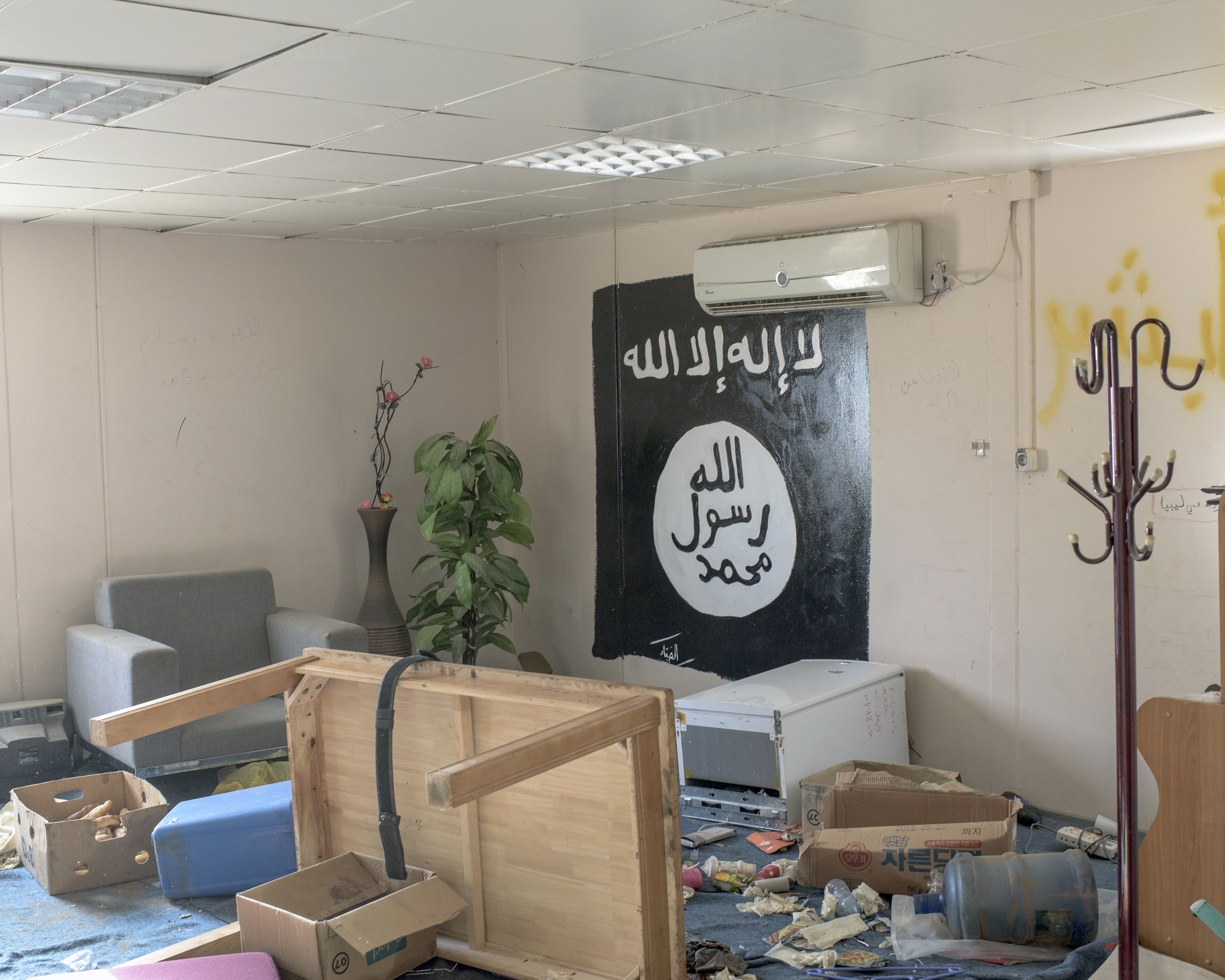 The black flag of ISIS  is painted on the wall of a living room in a complex of buildings occupied by ISIS fighters, Sirt, Libya, July 2016.