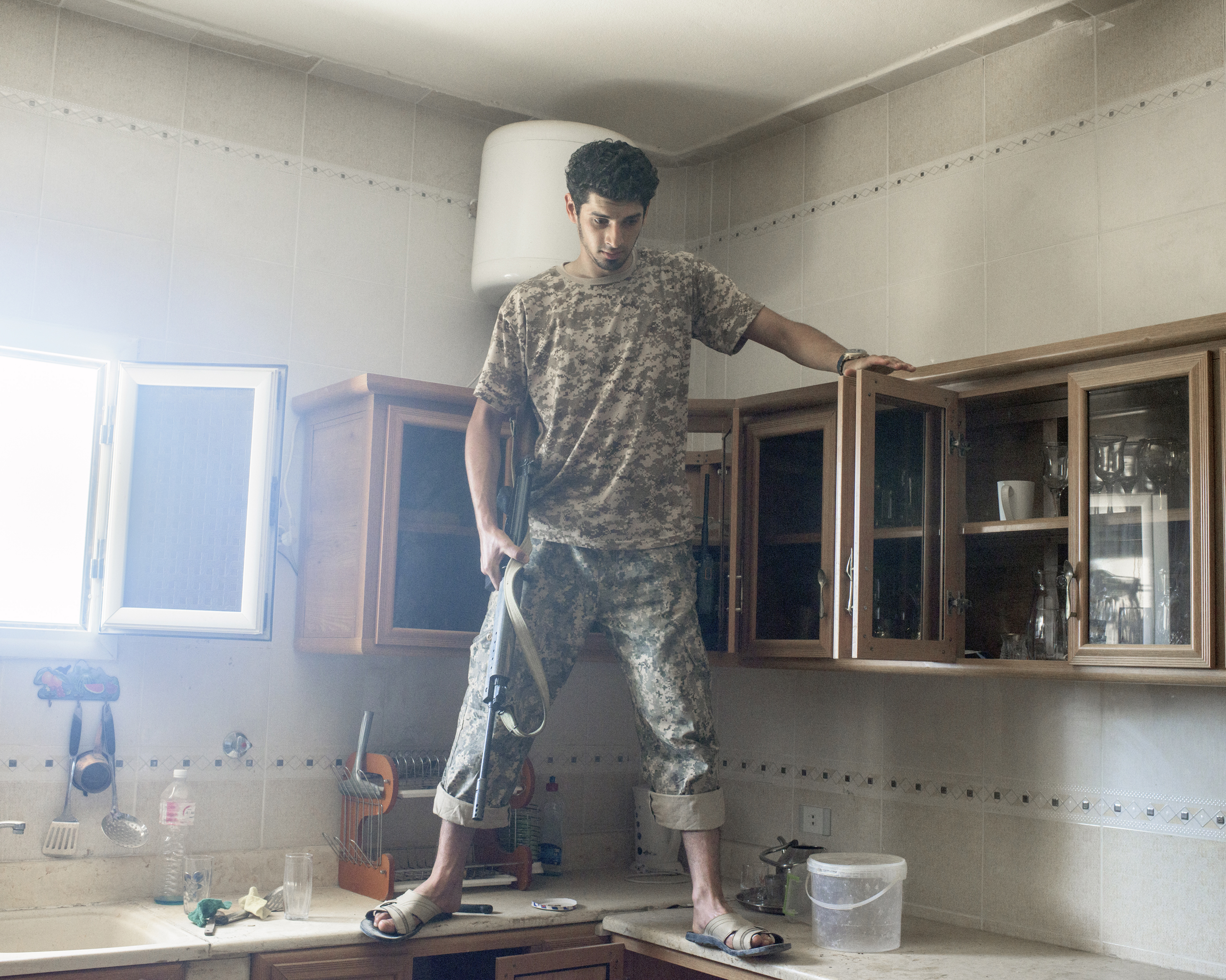 A Libyan fighter checks a kitchen for IEDs in a villa in a newly-liberated  district, Sirt, Libya, July 2016.