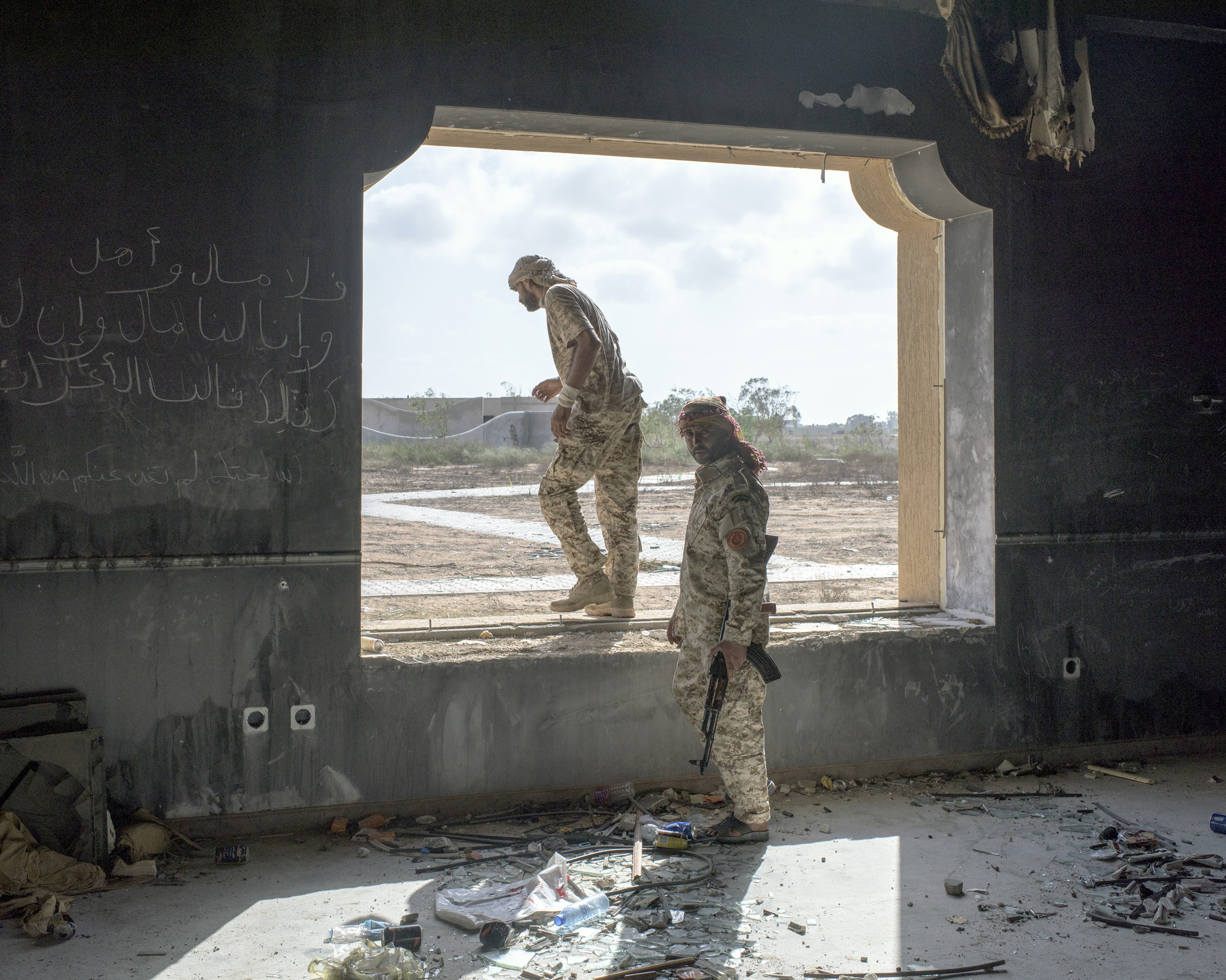 Two fighters on the frontline in a newly-captured building on the grounds of the Ougadougou Complex, a convention center, Sirt, Libya, July 2016.
