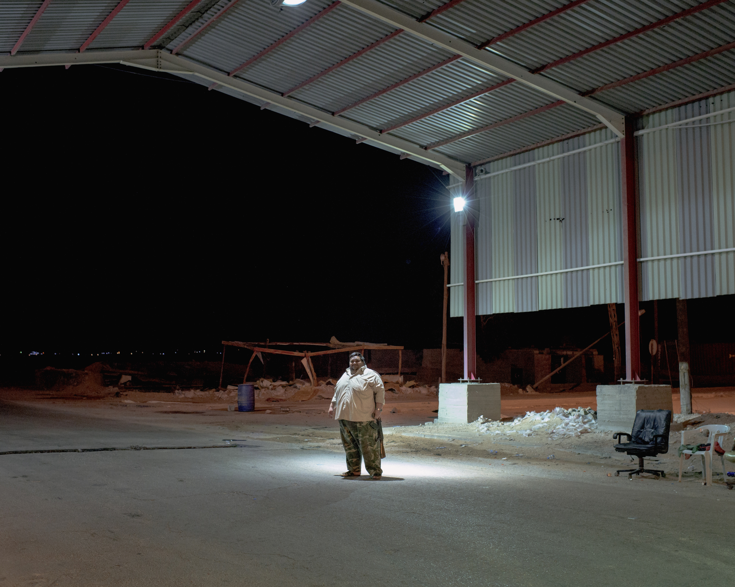 A Libyan fighter guards the Abu Grain checkpoint at night, July 2016.