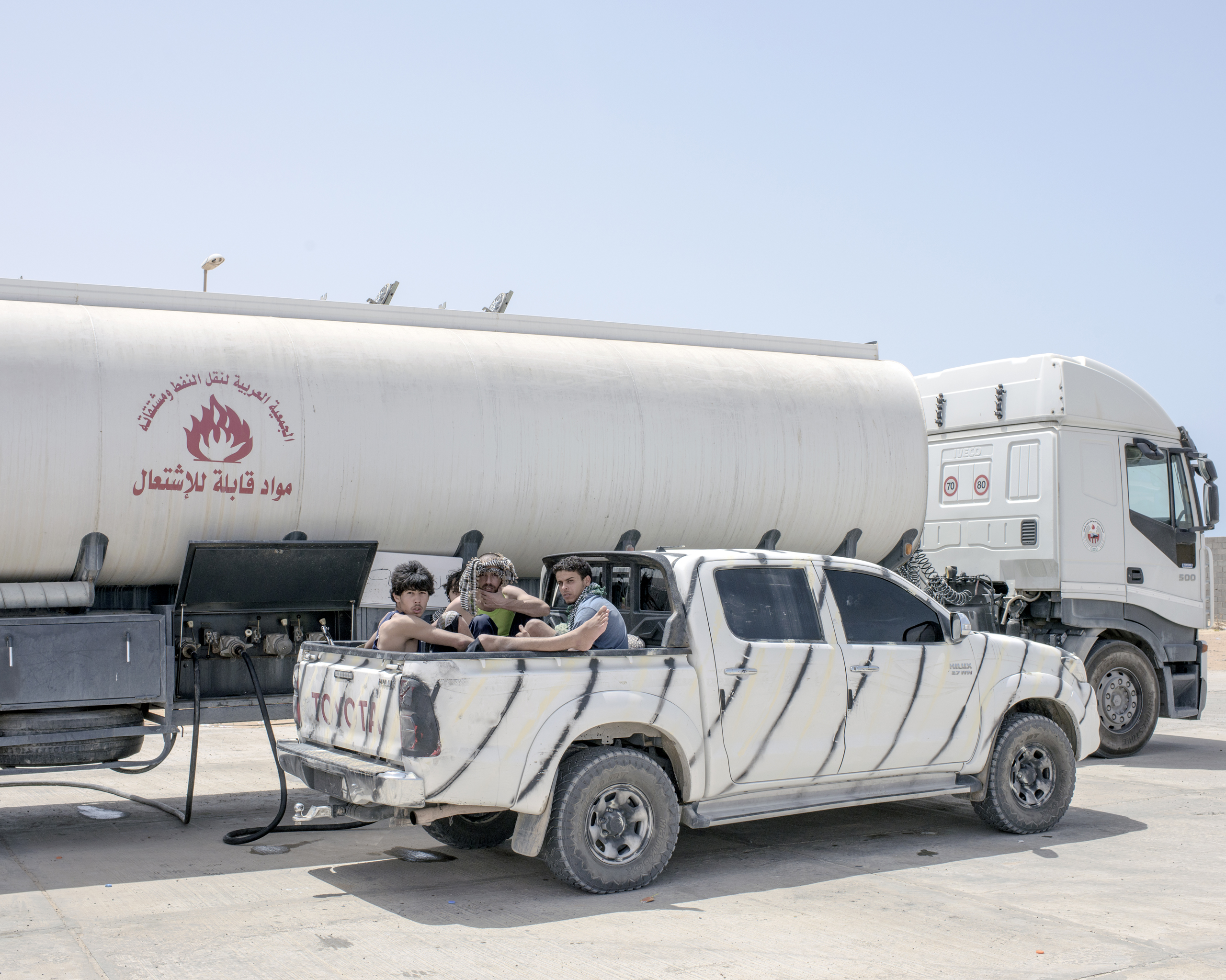 A group of Libyan fighters refuel their vehicle from a tanker at a petrol station outside Sirt, July 2016