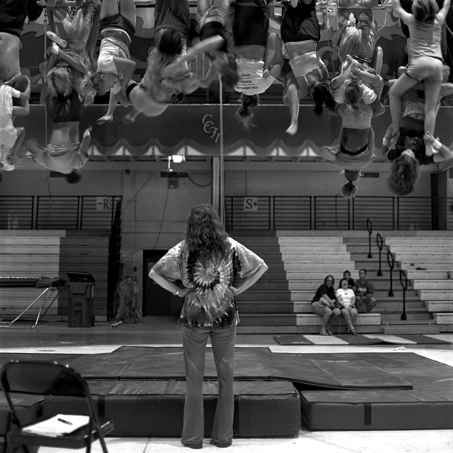 Lori Smith, a trainer for the Double 4 Lane act,  watches as laughing and giggling kids climb, using each other as ladders to get to the top. Parents of child performers often sit in the stands and watch the practice.