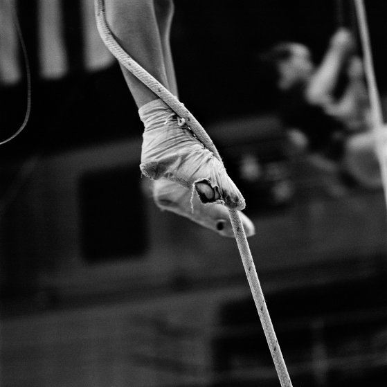 A performer climbs a rope to reach the single trapeze, wearing last year's custom-made performance slippers. Performers are required to buy their own slippers, but they are re-used for practice. Circus personnel viewed this image as a testament to how hard all the young kids practice, how dedicated they are, and how frugal.
