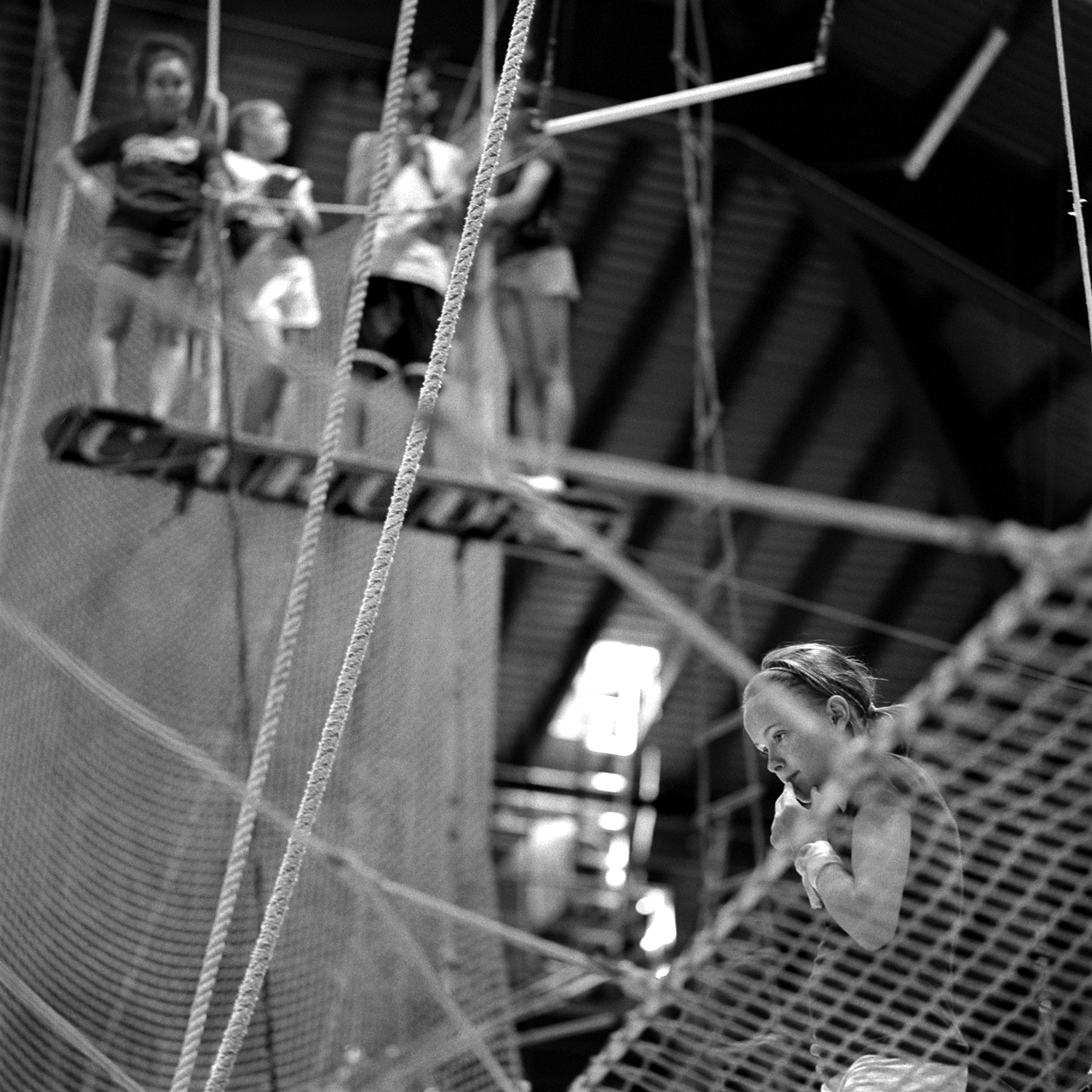 Josie Murphy, 13, ponders advice from her trainer on the flying trapeze while others await their turn to practice. For the most challenging acts, performers are selected earl, based on their potential and suitability.