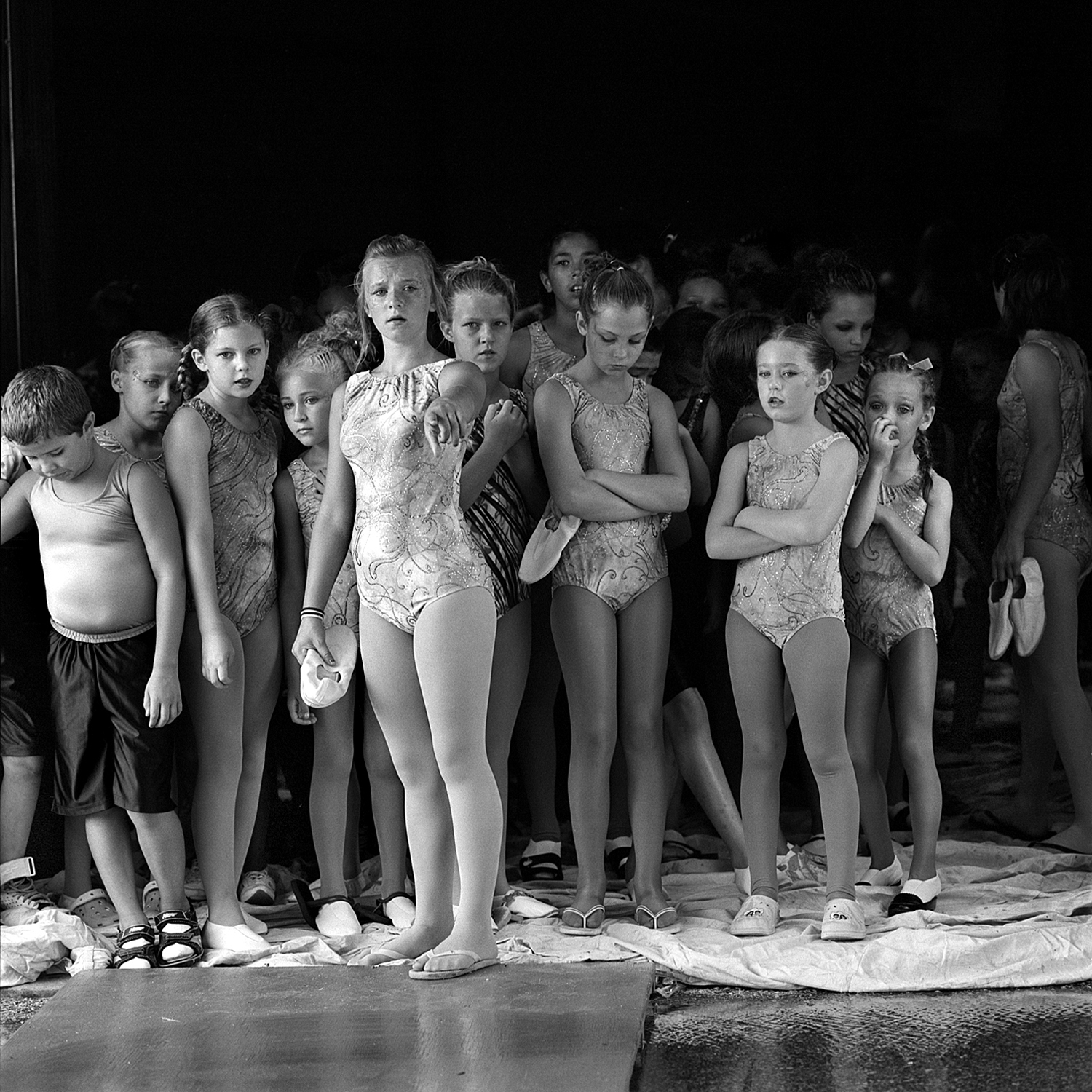 During a rainstorm, performers express concern about the flooding while waiting in the backlot area for their turn to enter the ring.