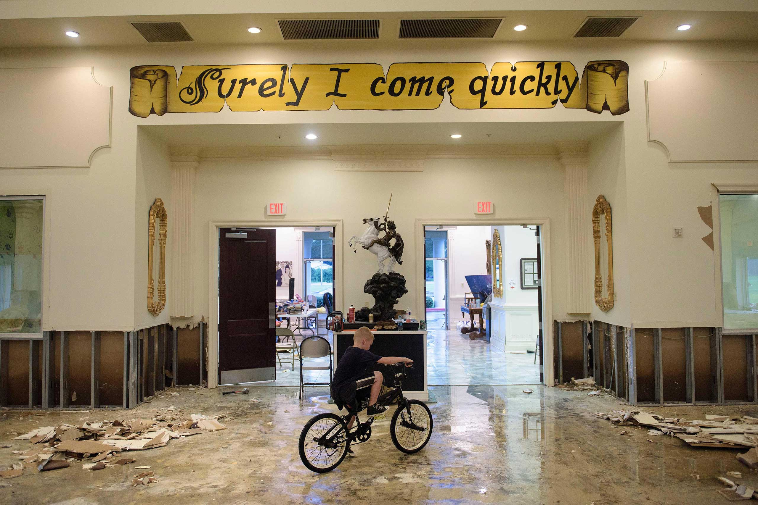 A boy rides his bike inside the flood-damaged Life Tabernacle Church in Baton Rouge, La., on Aug. 15, 2016.