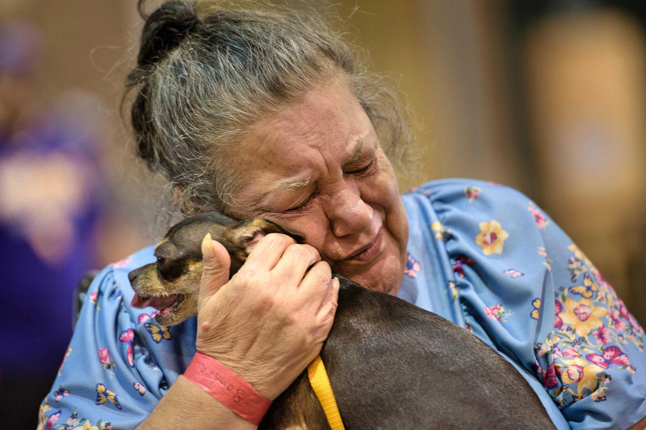 Sandra Montanaro holds her dog, Dixy, during one of two 20-minute daily visits at a temporary animal shelter the Lamar Dixon Expo Center, near a flood victims shelter, in Gonzales, La., on Aug. 16, 2016.