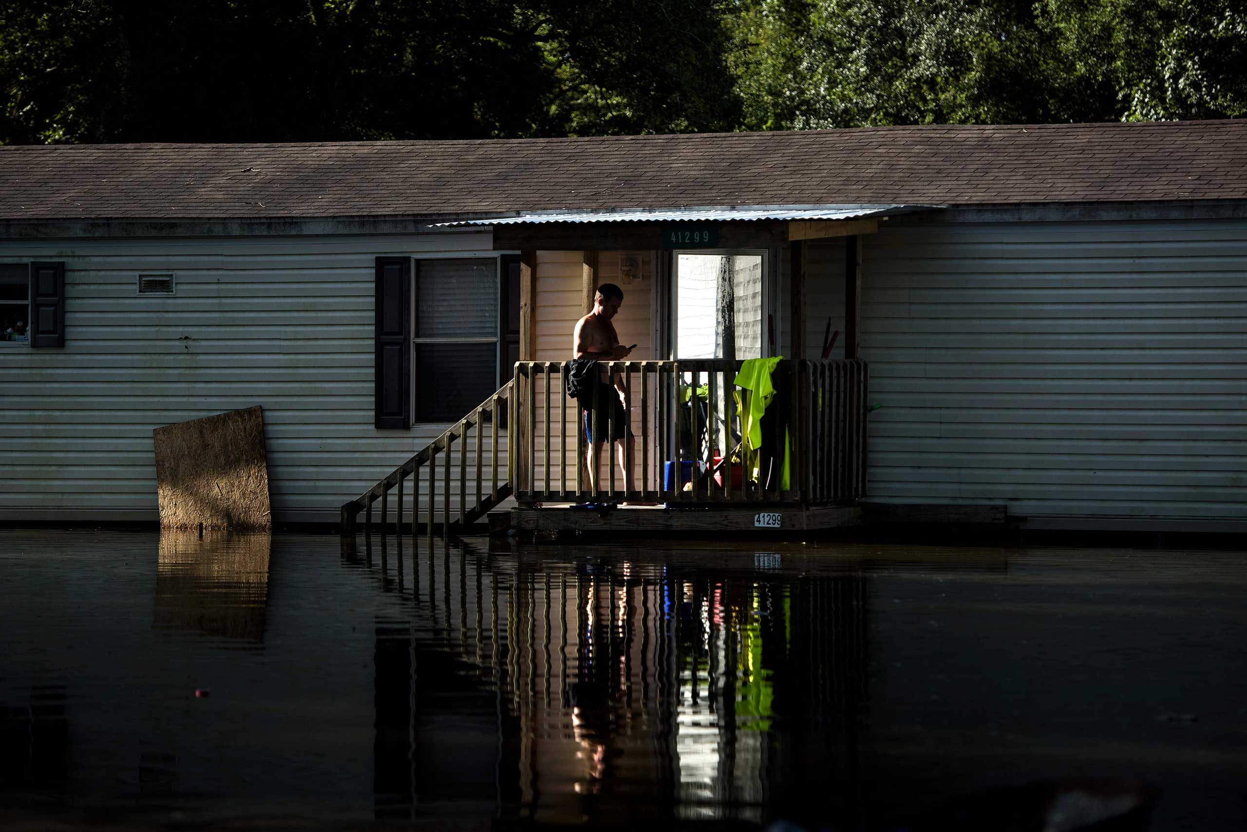 A man stands on the stairs os a home surrounded by floodwaters in Gonzales, La., on Aug. 16, 2016.
